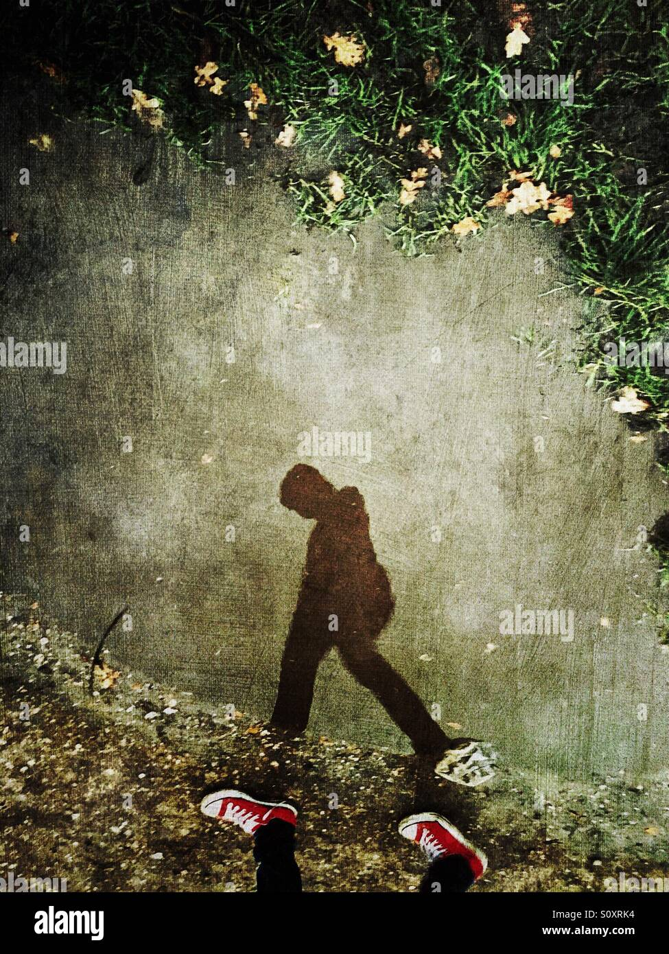Reflection of make youth walking with head down - Stock Image
