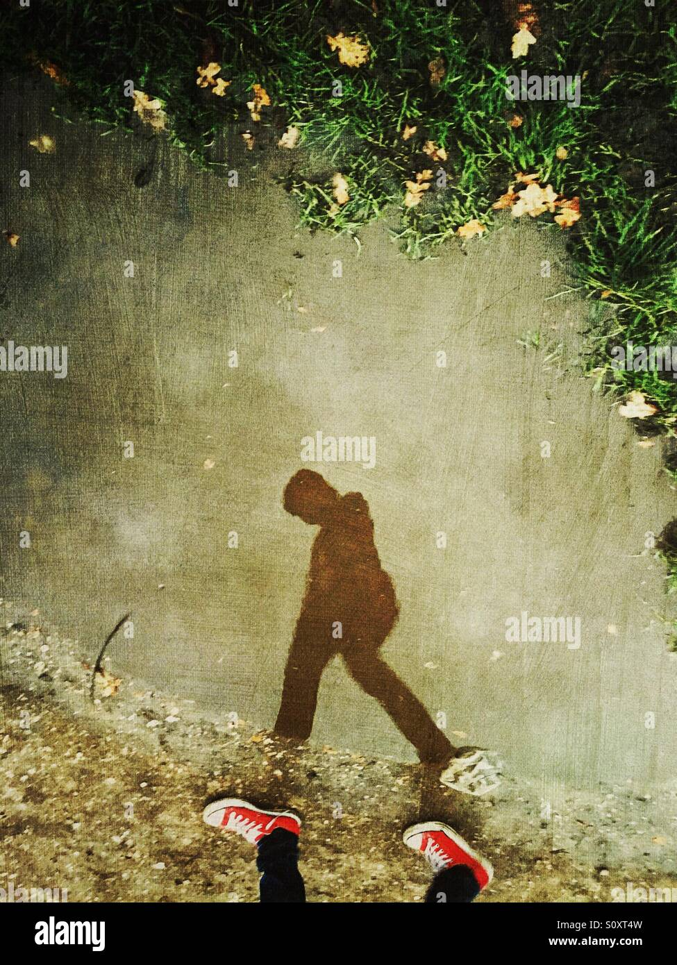 Boy silhouette walking with red converse - Stock Image