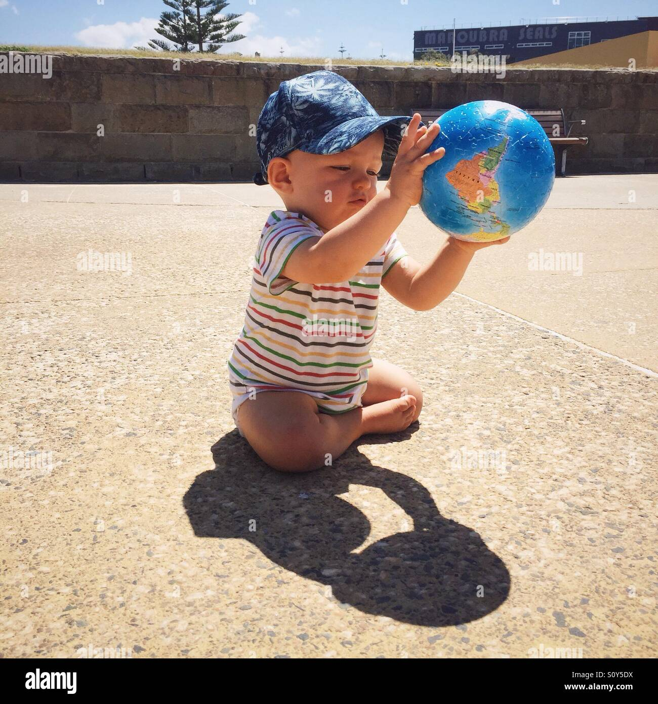 Child playing with globe ball - Stock Image