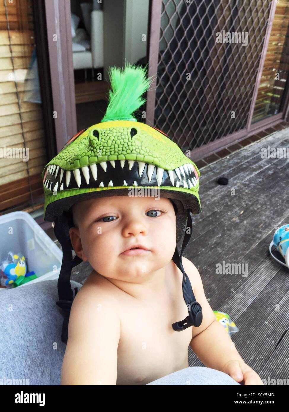 Cute little boy with his dinosaur helmet on - Stock Image