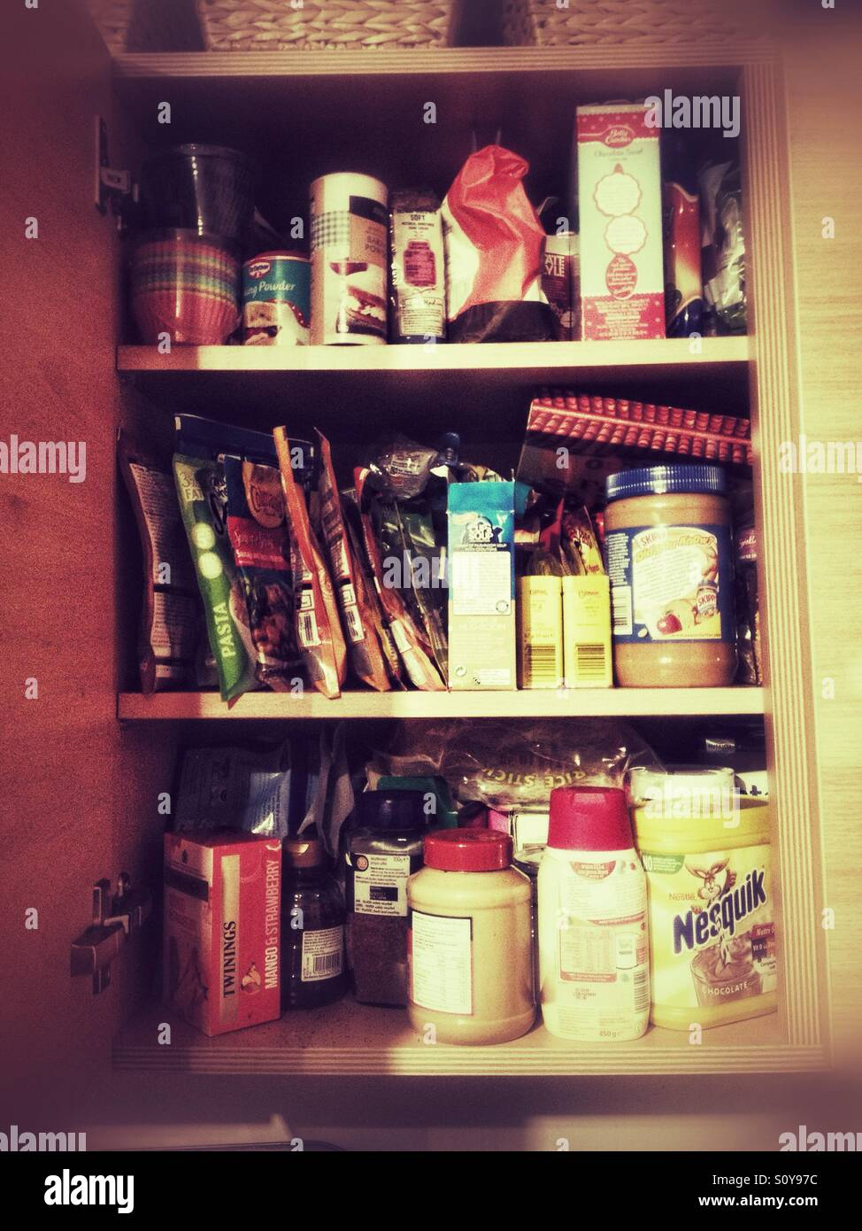 A kitchen cupboard full of food. Stock Photo