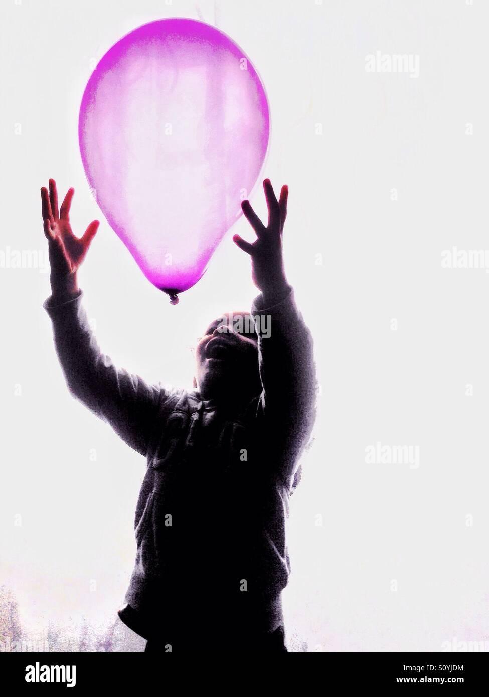 Boy catching a Pink balloon. Stock Photo