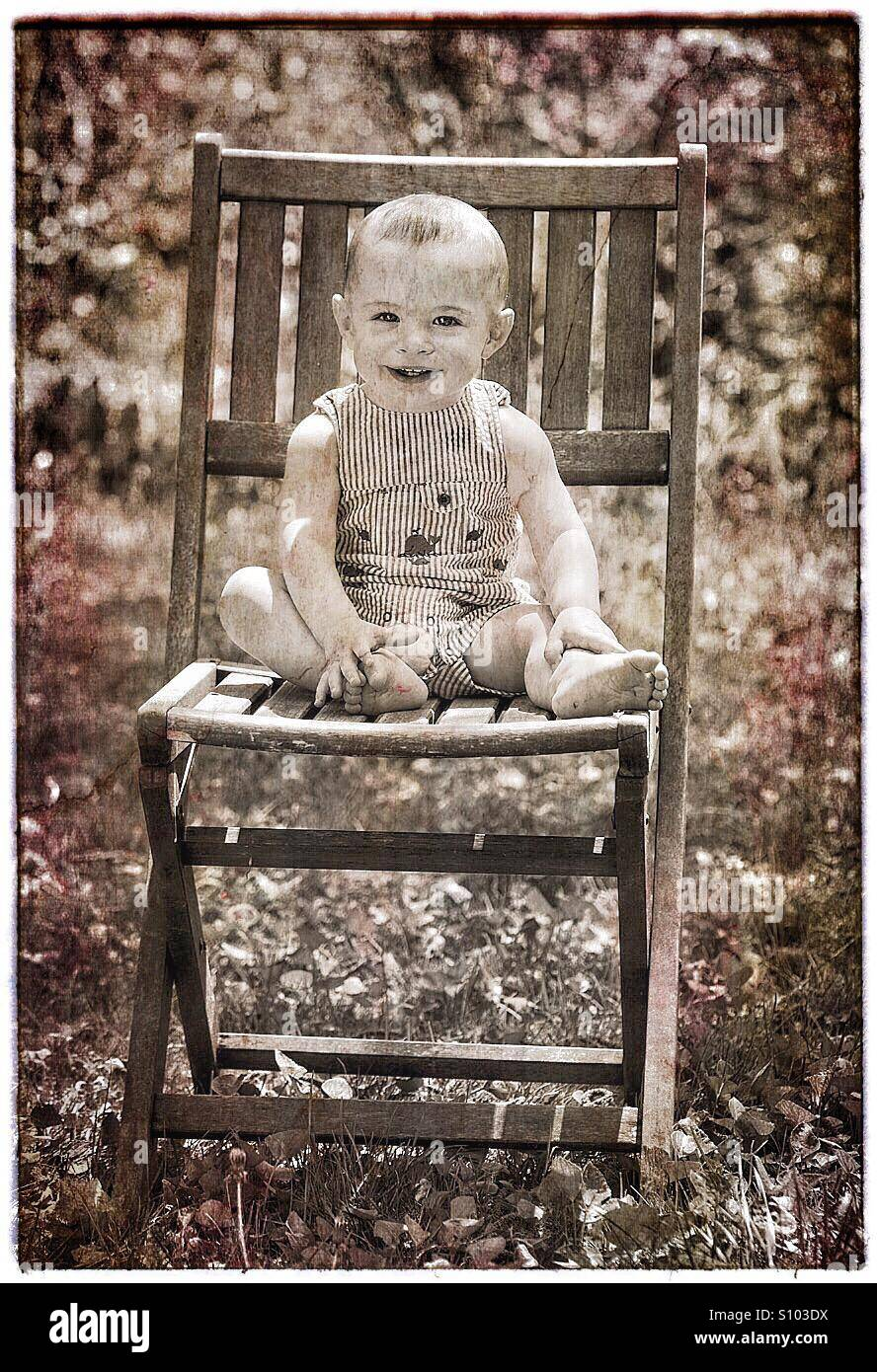 Baby with big smile sitting on chair outside. - Stock Image