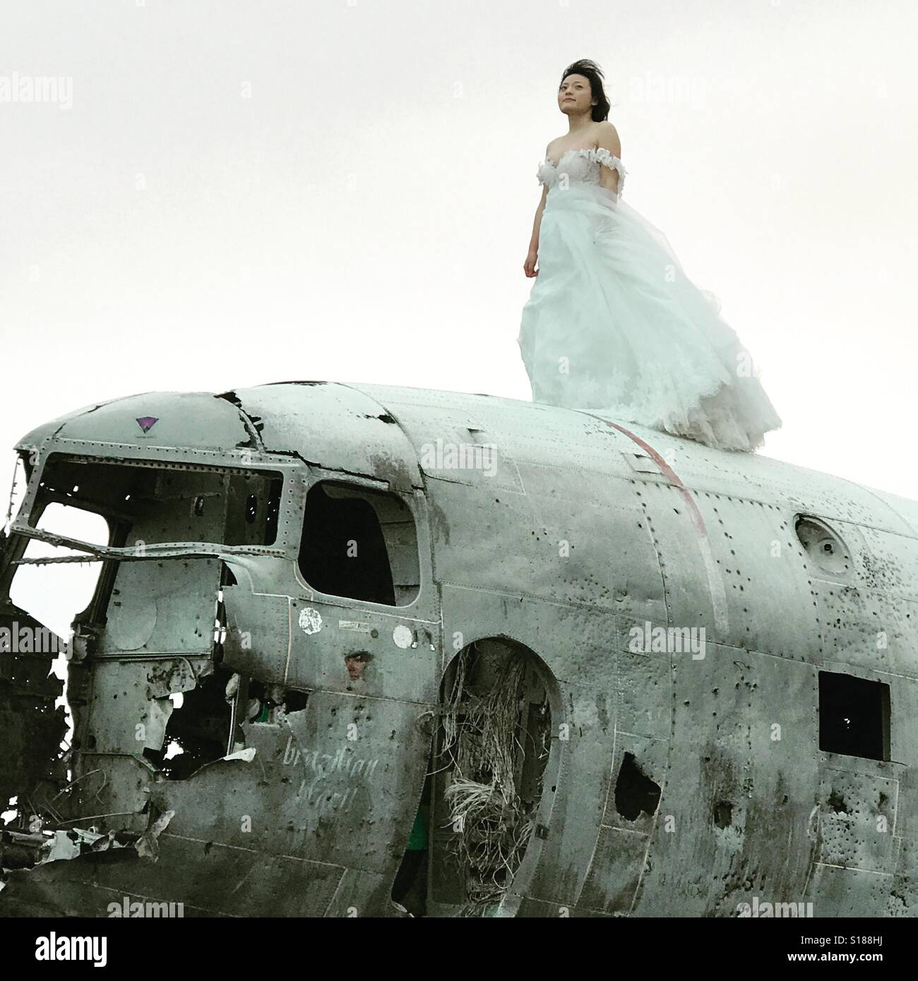 Bride on top of the plane wreck in Iceland Stock Photo