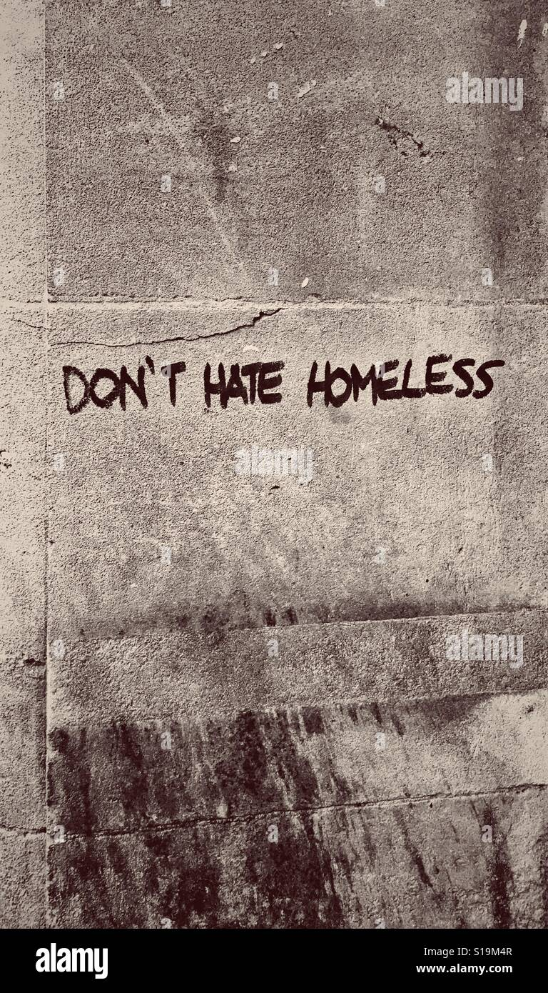 A sepia photograph of graffiti reading 'DON'T HATE HOMELESS' on a wall in a town in the UK - Stock Image