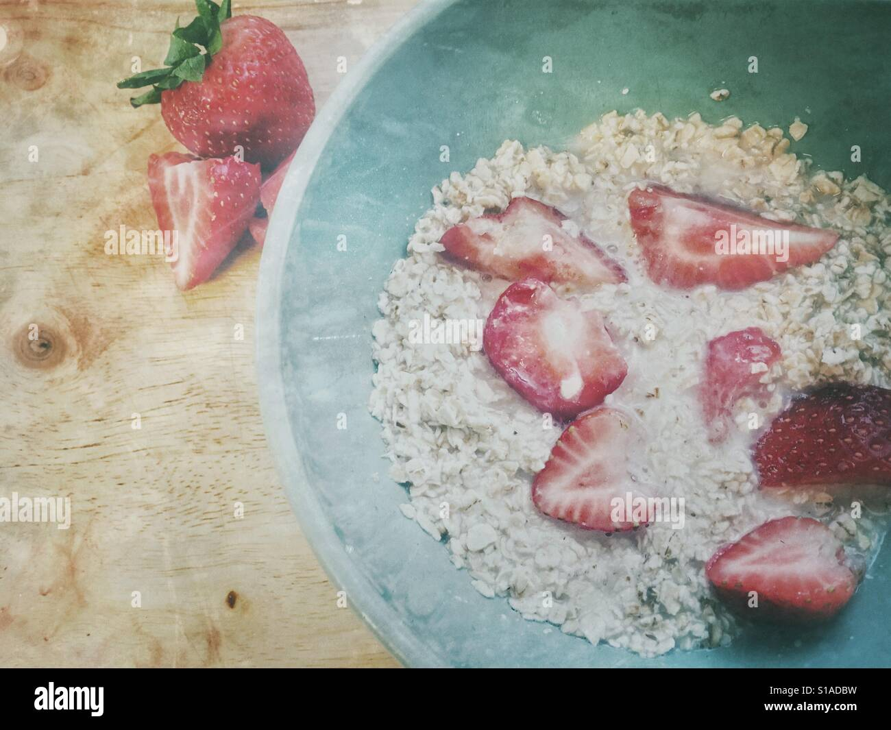 Good morning porridge for breakfast red ripe strawberries oatmeal and almond milk in a green aqua bowl on wood vintage Stock Photo