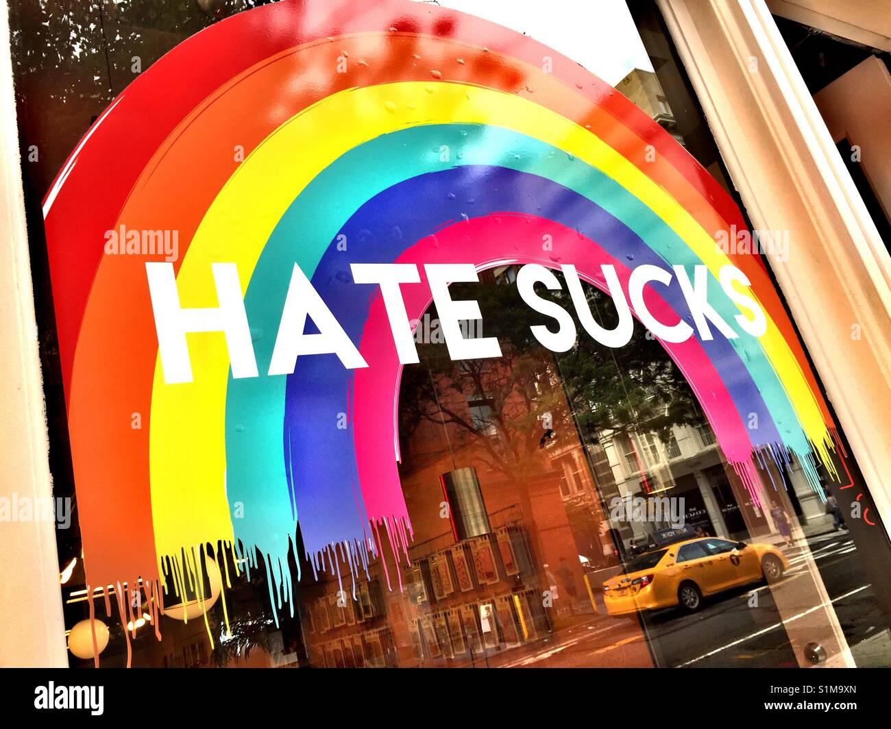 Hate sucks and rainbow sign on store window, NYC, USA - Stock Image