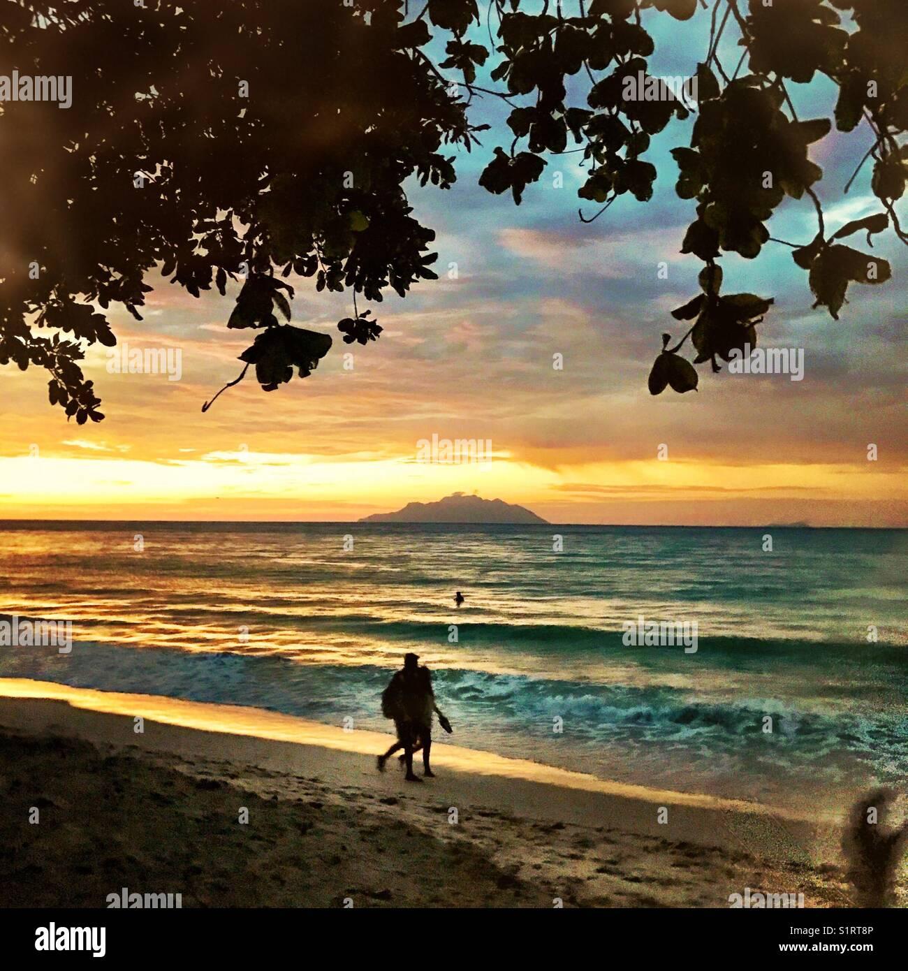 People on Seychelles beach Beau Vallon sunset - Stock Image