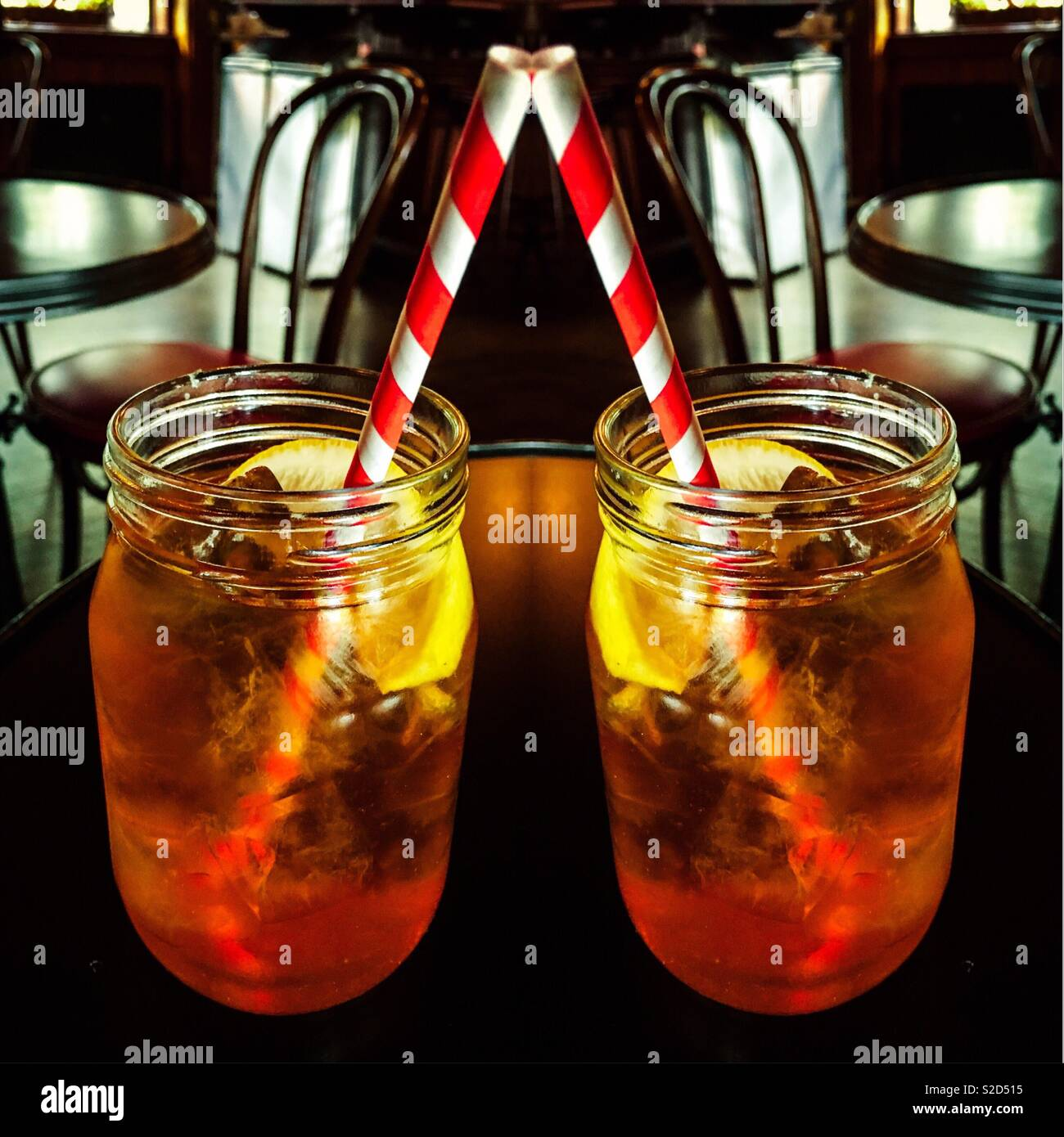 Double exposure iced tea in mason jar glasses with eco friendly paper straws. Europe announced a ban on some plastics including straws.These brightly colored paper straws are fun an good for the earth Stock Photo