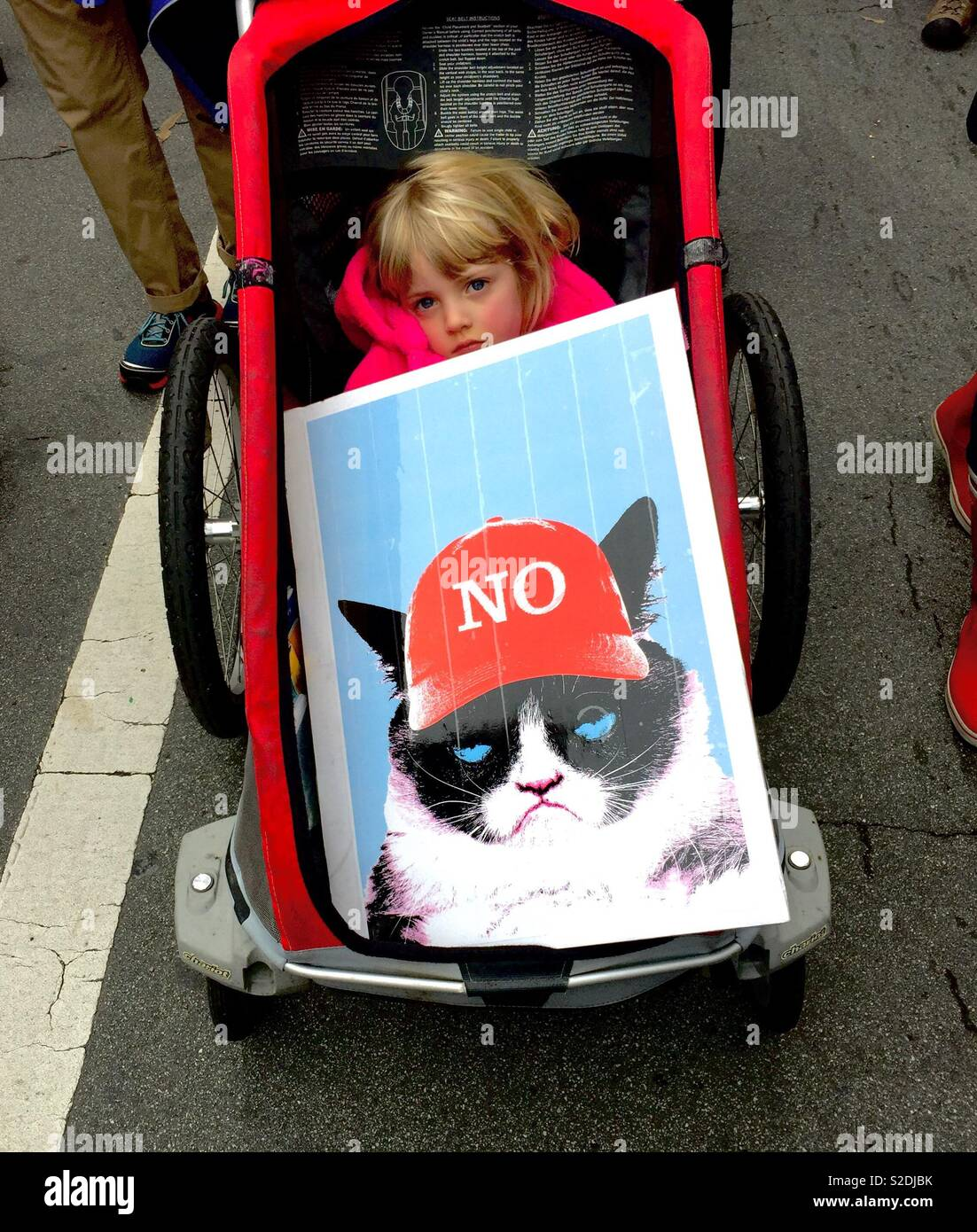 Tired blonde child in stroller behind a protest sign of Grumpy Cat wearing a red baseball cap that says NO, instead of a MAGA hat. Women's March 2017. Oakland, California, USA Stock Photo