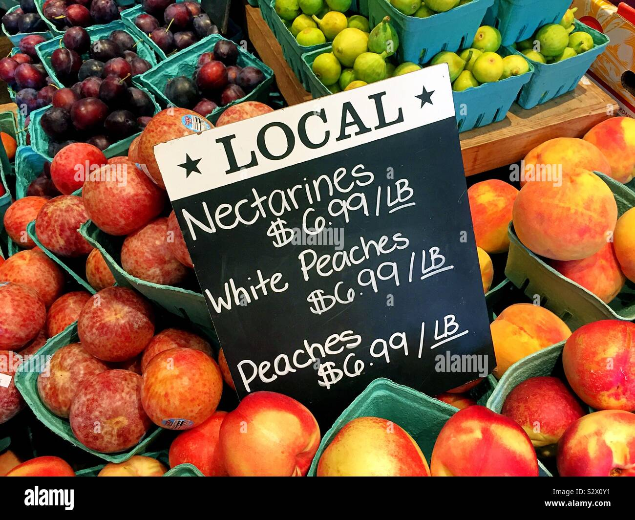 Local farm to table nectarines and peaches for sale in a farmers market, USA Stock Photo