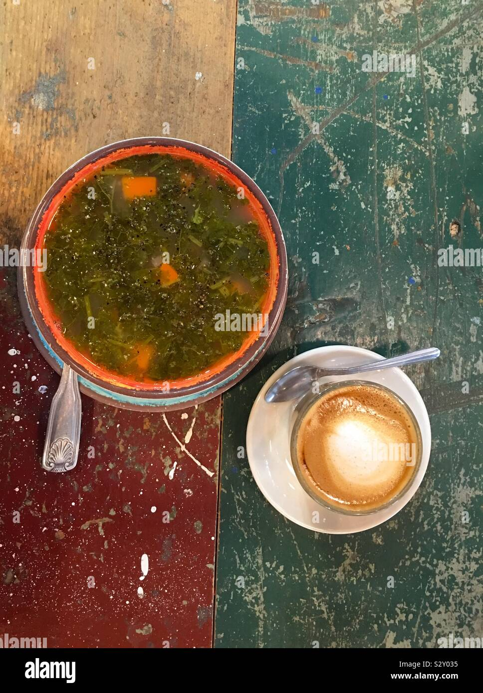 Healthy kale vegetable soup and cortado coffee that is half espresso half milk. Grunge scratch paint wood table flat lay. Stock Photo