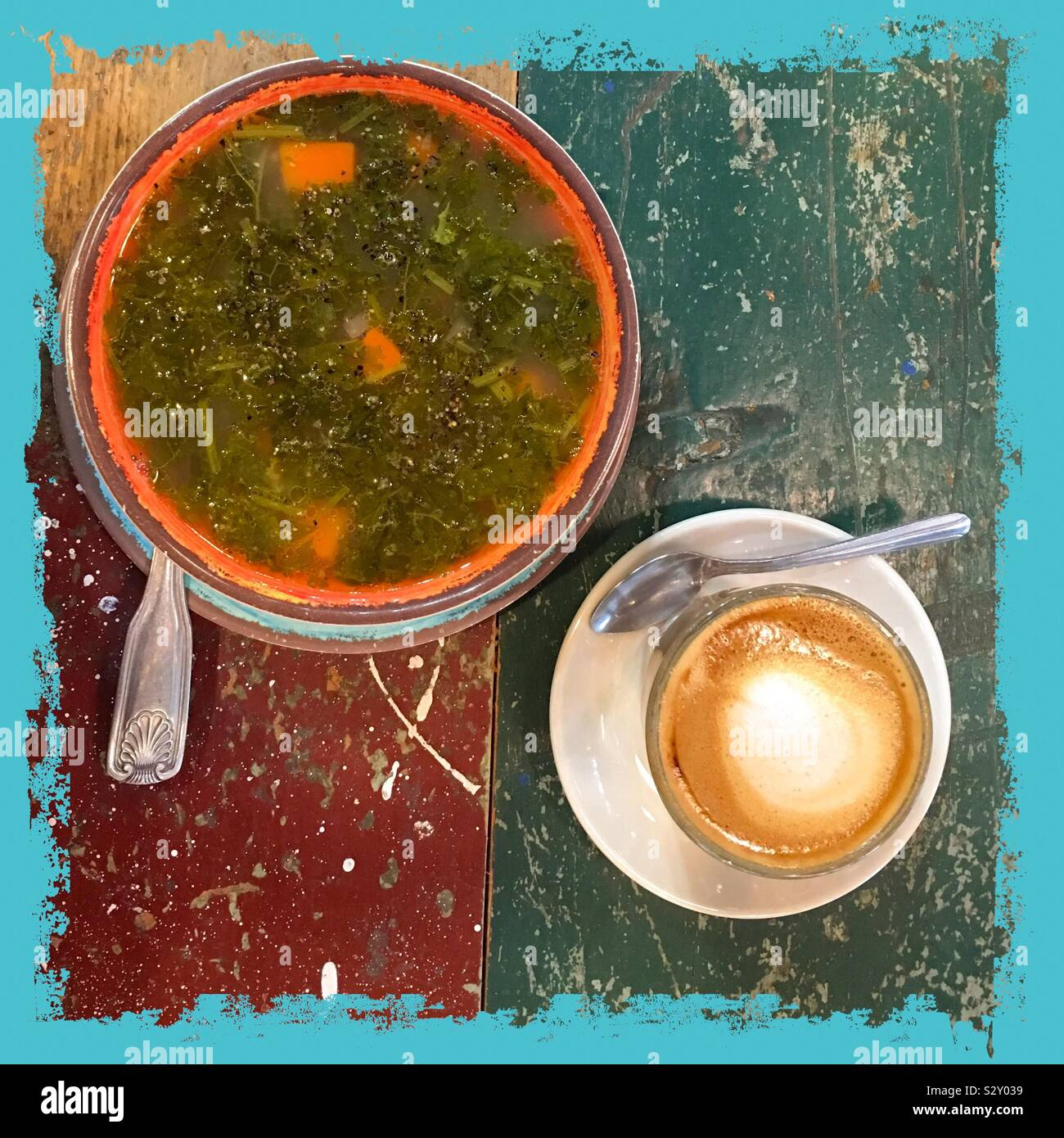 Framed square healthy kale veggie soup for fall with trendy cortado, coffee half milk half espresso. Flat lay still life food from above. Scratched colorful paint table wooden surface. Stock Photo