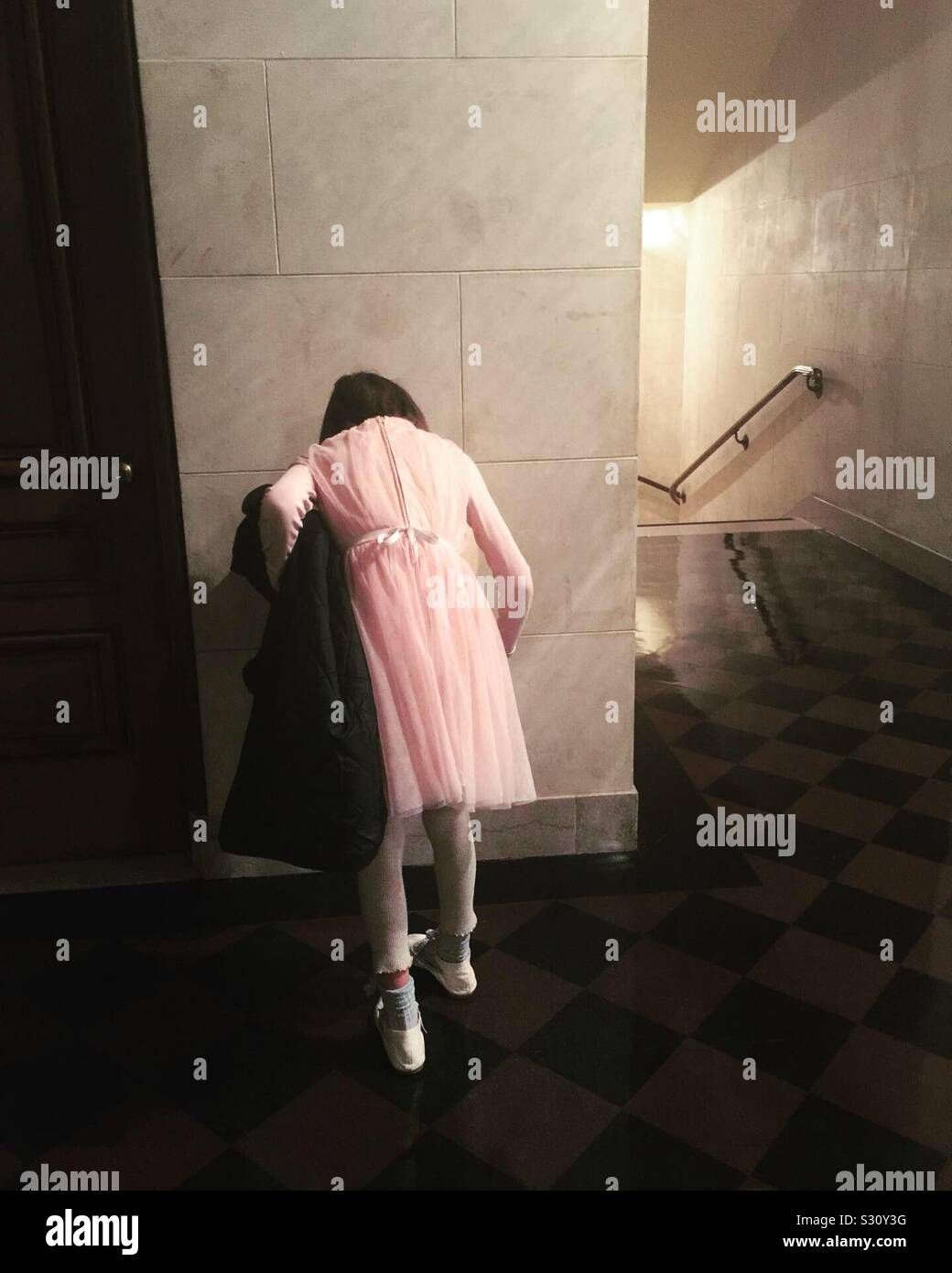 Girl wearing fancy pink dress at a drinking fountain at the SF War Memorial Opera House at intermission. Stock Photo