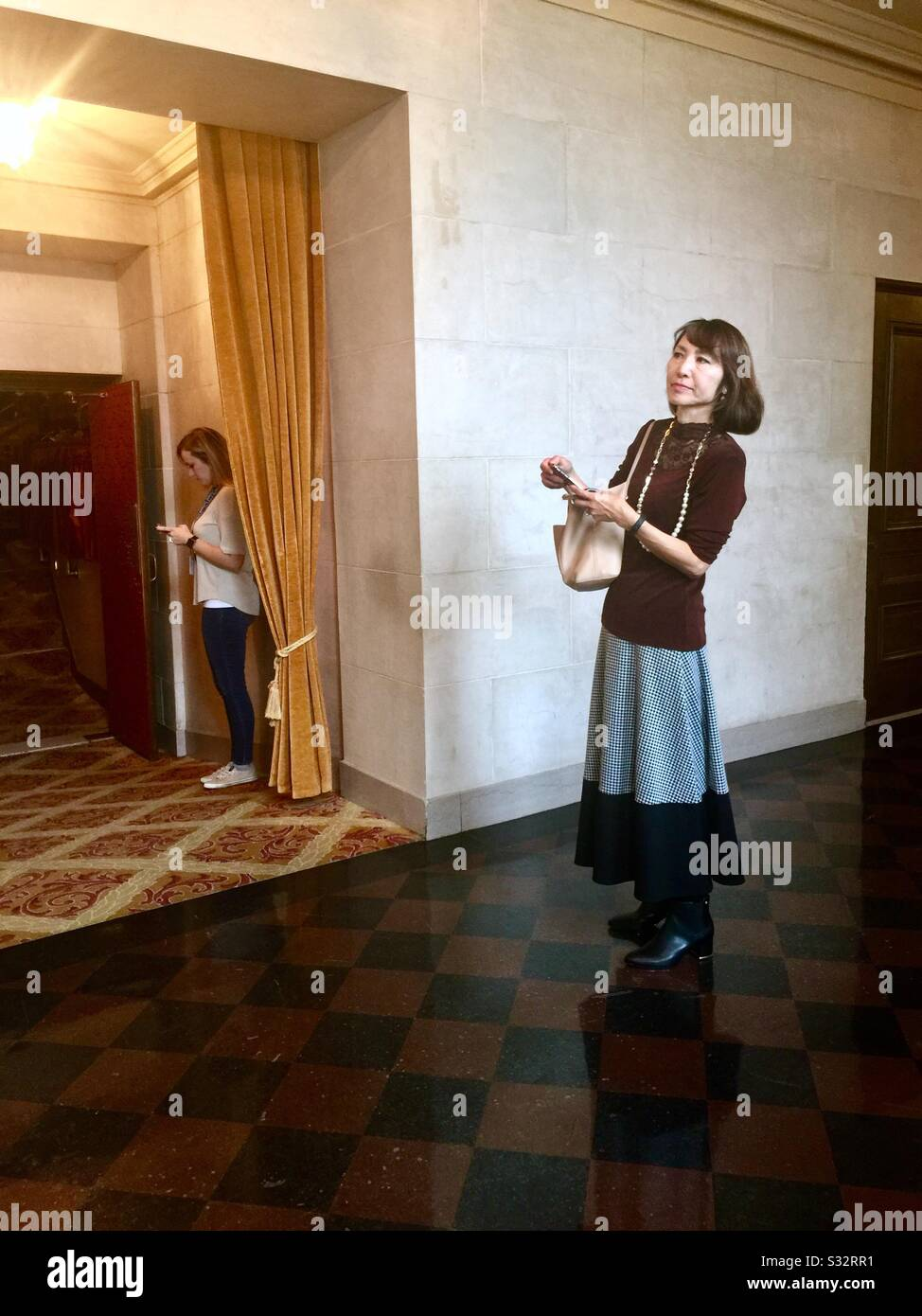 Two women waiting in the halls at the elegant War Memorial Opera House during intermission. One woman waiting for a friend, the other looking at her cell phone. San Francisco, California. Stock Photo