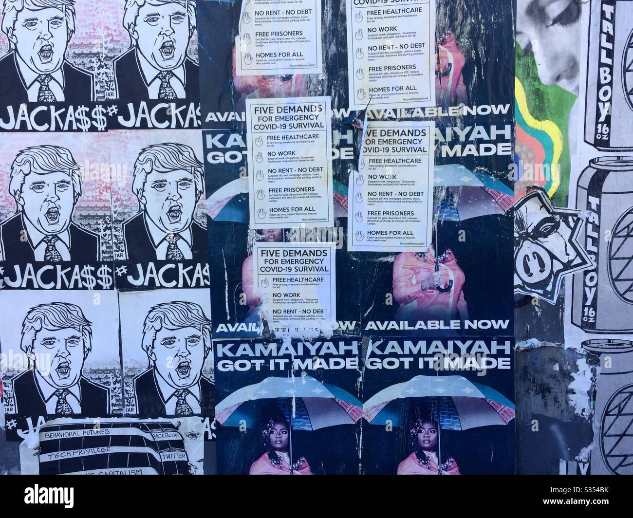Postered wall which includes anti-Trump JackAss artwork, Coronavirus demands and Kamaiyah Got It Made poster. Oakland, California Stock Photo
