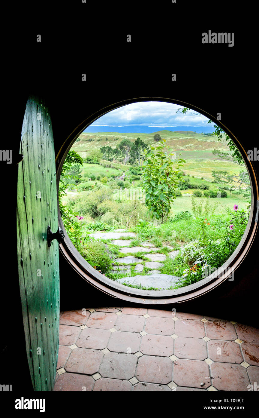 open-circular-door-of-hobbit-hole-at-hobbiton-movie-set-in-the-waikato-region-of-new-zealand-north-island-looking-out-to-the-shire-countryside-T09BJT.jpg