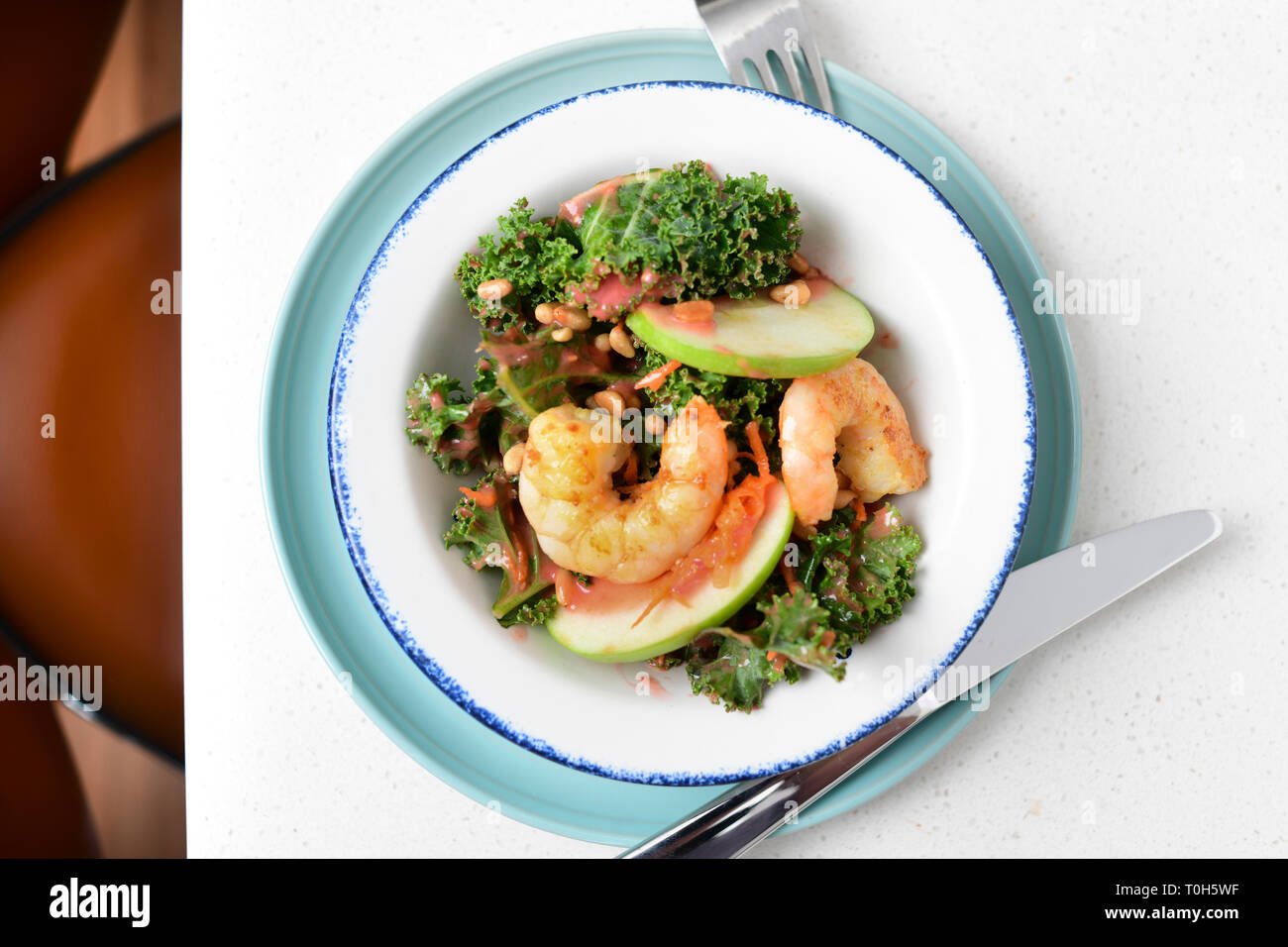 food-kale-salad-with-shrimp-and-apple-on-it-in-a-home-kitchen-T0H5WF.jpg