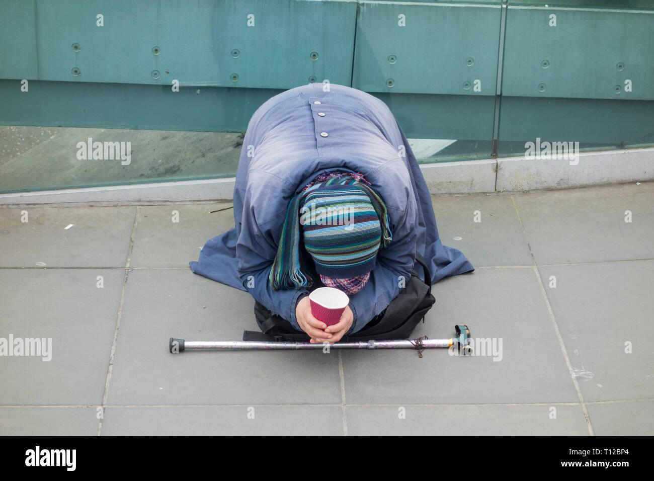 A prostate Eastern European woman begging outside the Tate Modern on the Millenium Bridge, London, UK Stock Photo