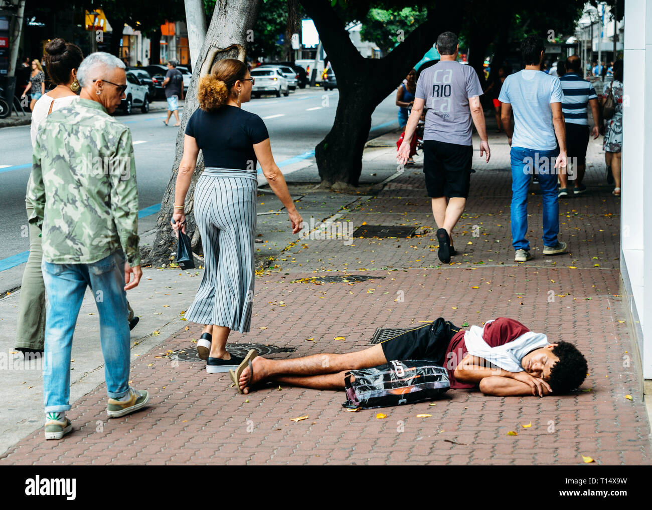 rio-de-janeiro-brazil-march-23-2019-homeless-young-man-sleeping-rough-while-pedestrians-walk-next-to-him-on-busy-pedestrian-sidewalk-in-the-wealth-T14X9W.jpg