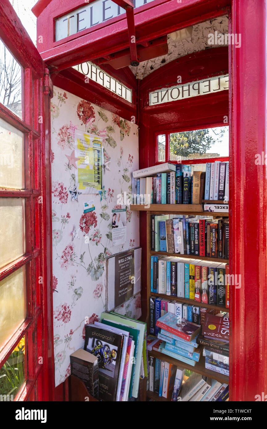 Old GPO telephone box used as a free book store in Fortescue, Sidmouth, Devon, UK. Stock Photo