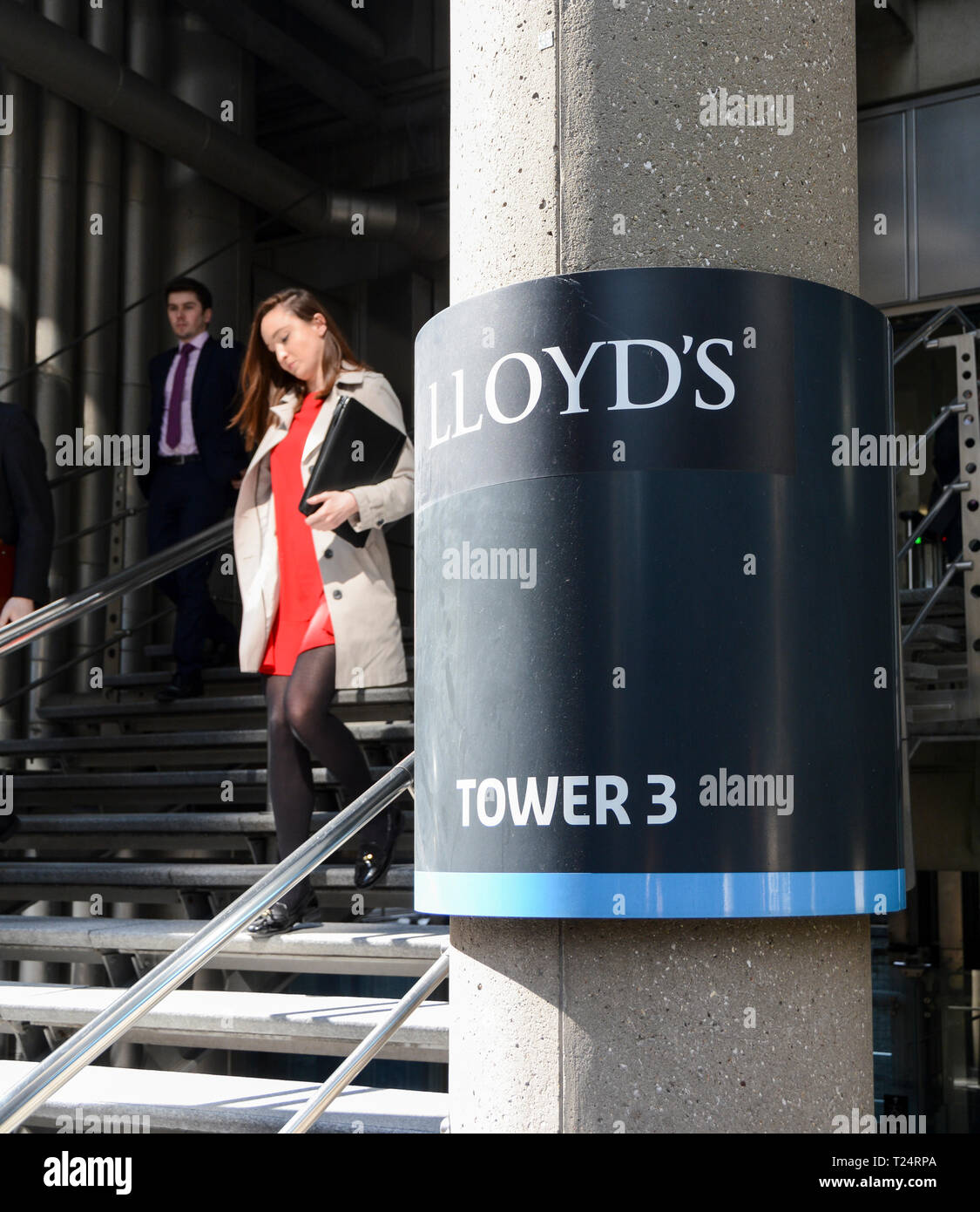 A young businesswoman leaving The Lloyd's Building, Tower 3, Lime Street, City of London, U.K. Stock Photo