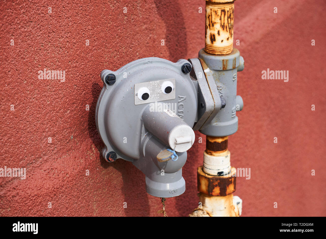 Pipes with googly eyes on them to make a funny face, outside a building with a red wall in Provo, Utah, USA. Stock Photo