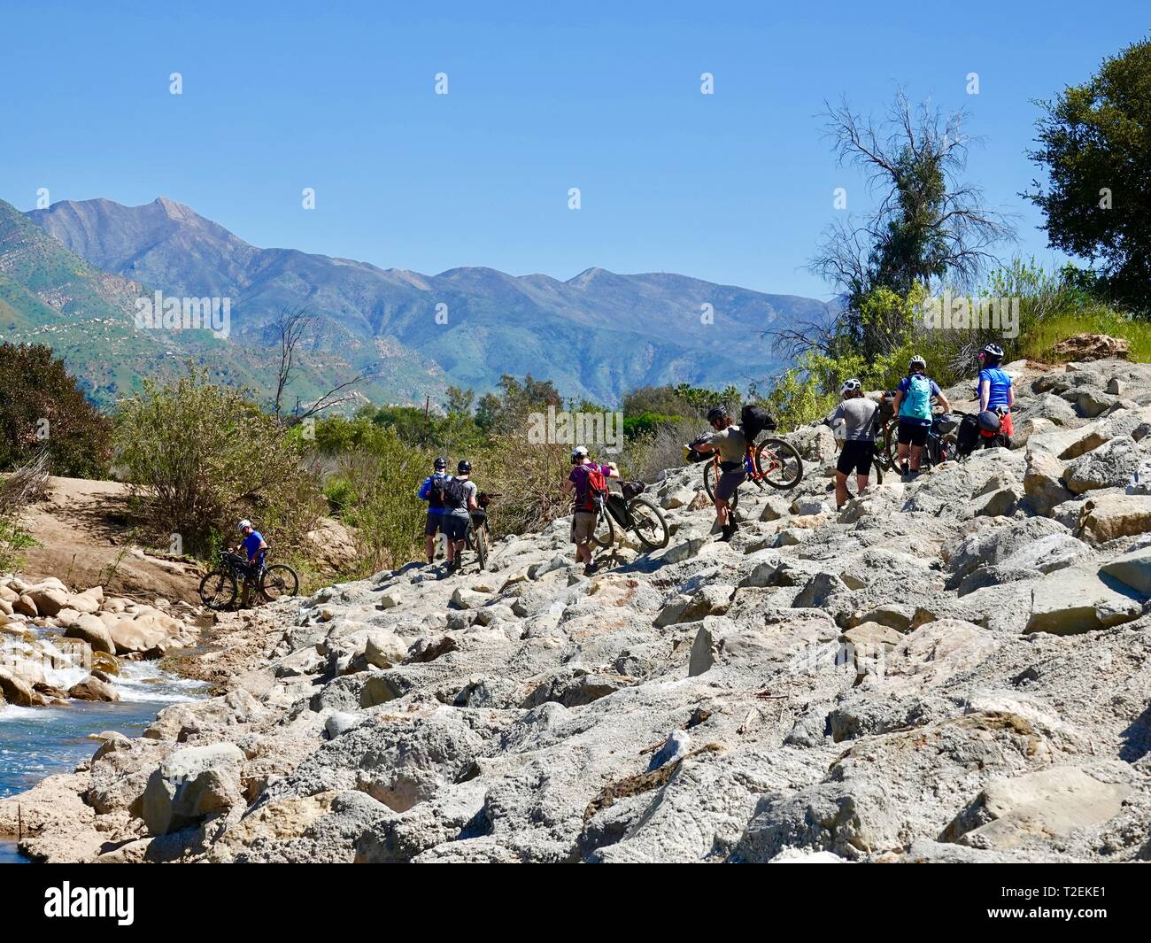group-of-mountain-bikers-carrying-their-