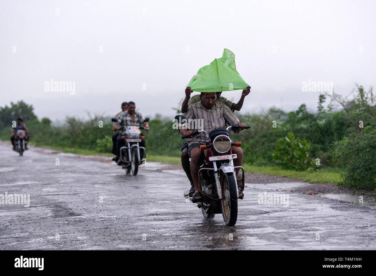 Bikers protecting with plastic bag the heavy rain in Rajasthan, India Stock Photo