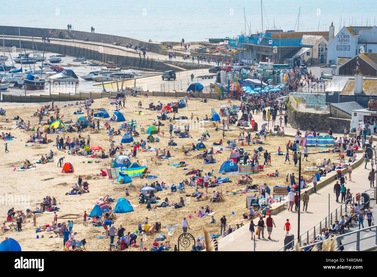 Lyme Regis, Dorset, UK. 18th April 2019. UK Weather: Crowds of holidaymakers and beachgoers flock to the picturesque beach at the seaside resort of Lyme Regis to bask in scorching hot sunshine. The balmy conditions are expected to continue with temperatures soaring over the Easter Holiday Bank Holiday Weekend. Credit: Celia McMahon/Alamy Live News. Stock Photo