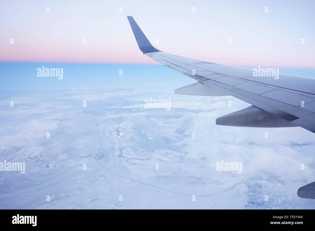Airplane wing over snowy earth in early morning, daybreak, dawn. Pastel earth and sky with pink horizon. Stock Photo