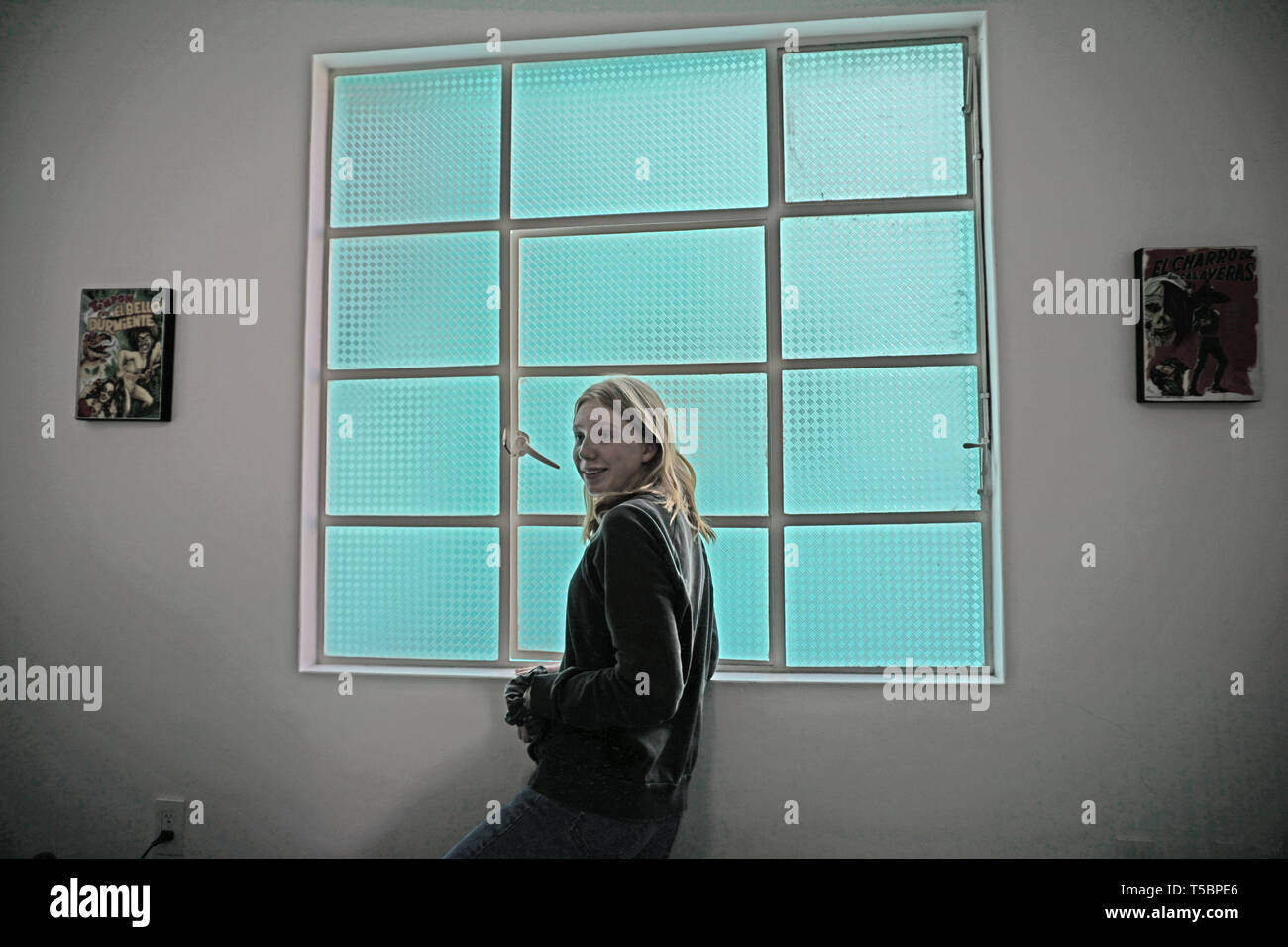 Girl in front of twelve-paned frosted glass turquoise-colored window. Stock Photo