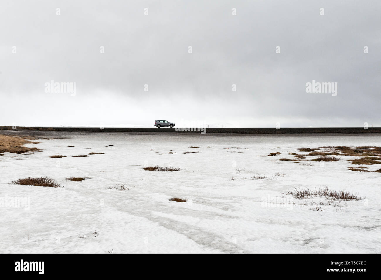 car-driving-on-a-road-beside-a-frozen-lake-in-iceland-T5C7BG.jpg