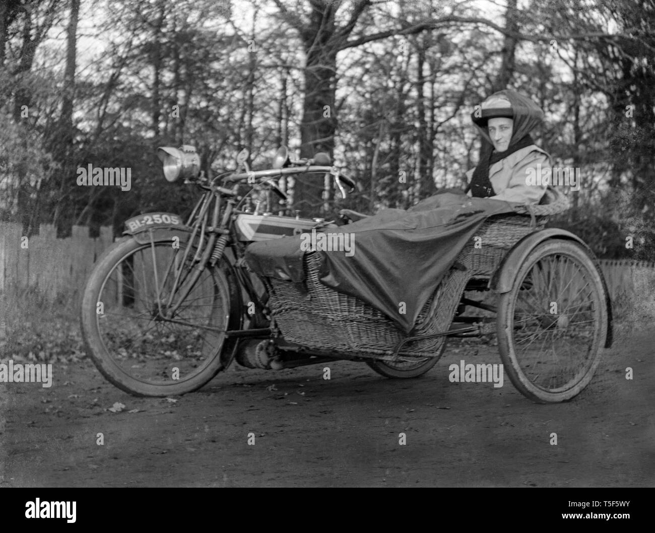 A period photograph of a lady sitting in the side car of a vintage Motorcycle and side car. The side car is made from wicker. Stock Photo