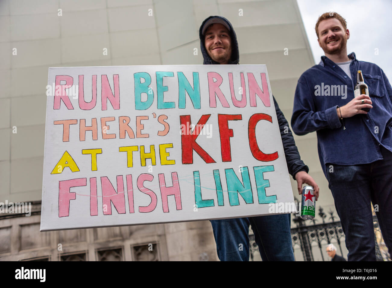 supporters-of-a-runner-in-the-london-marathon-2019-with-humorous-motivational-sign-saying-run-ben-run-theres-kfc-at-the-finish-line-placard-T6J016.jpg
