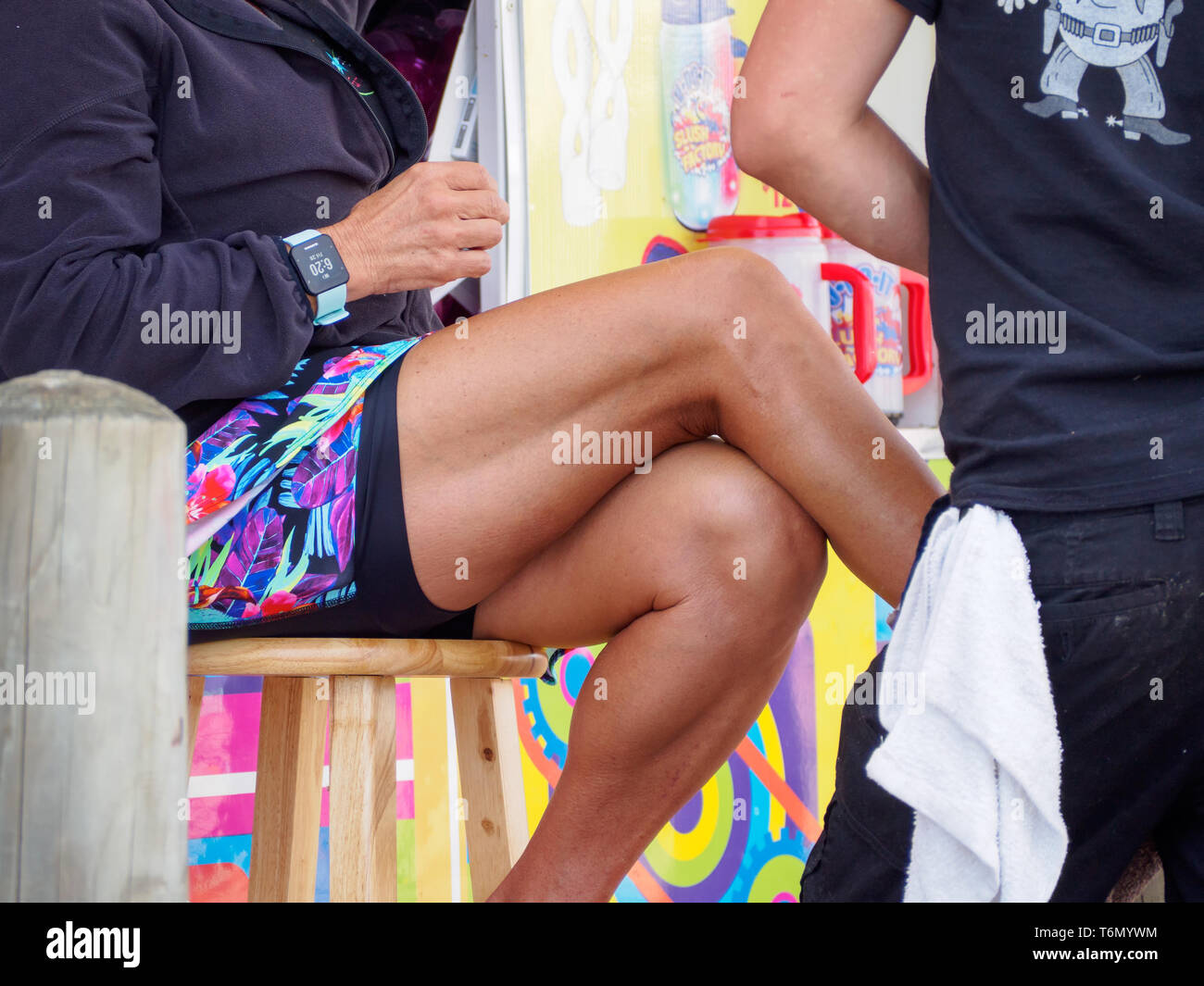The tanned, crossed legs of a stool seated female vendor at the 2019 Texas Sandfest in Port Aransas, Texas USA. Stock Photo