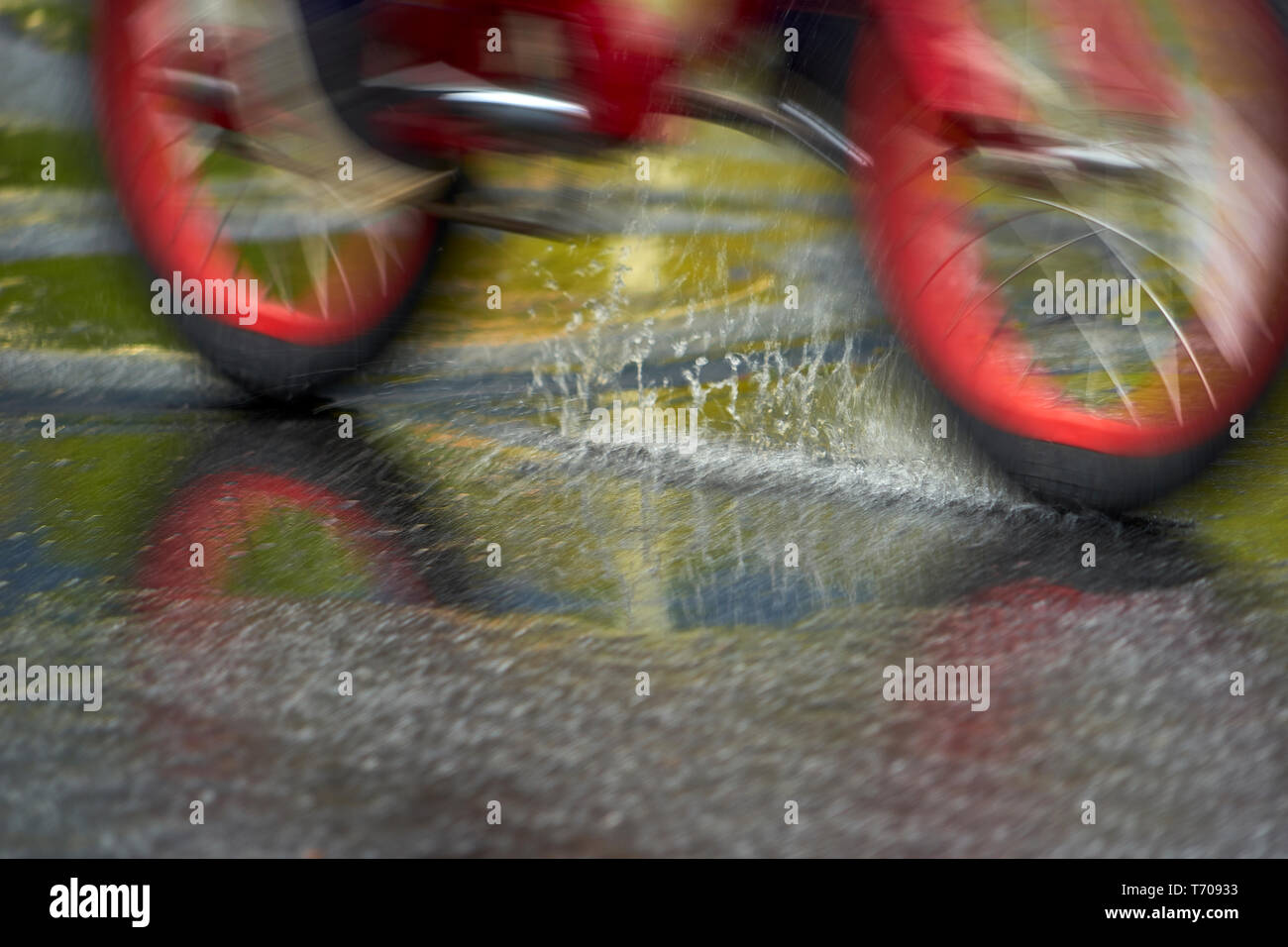 a-kid-rides-bike-on-street-pavement-through-rain-puddle-T70933.jpg