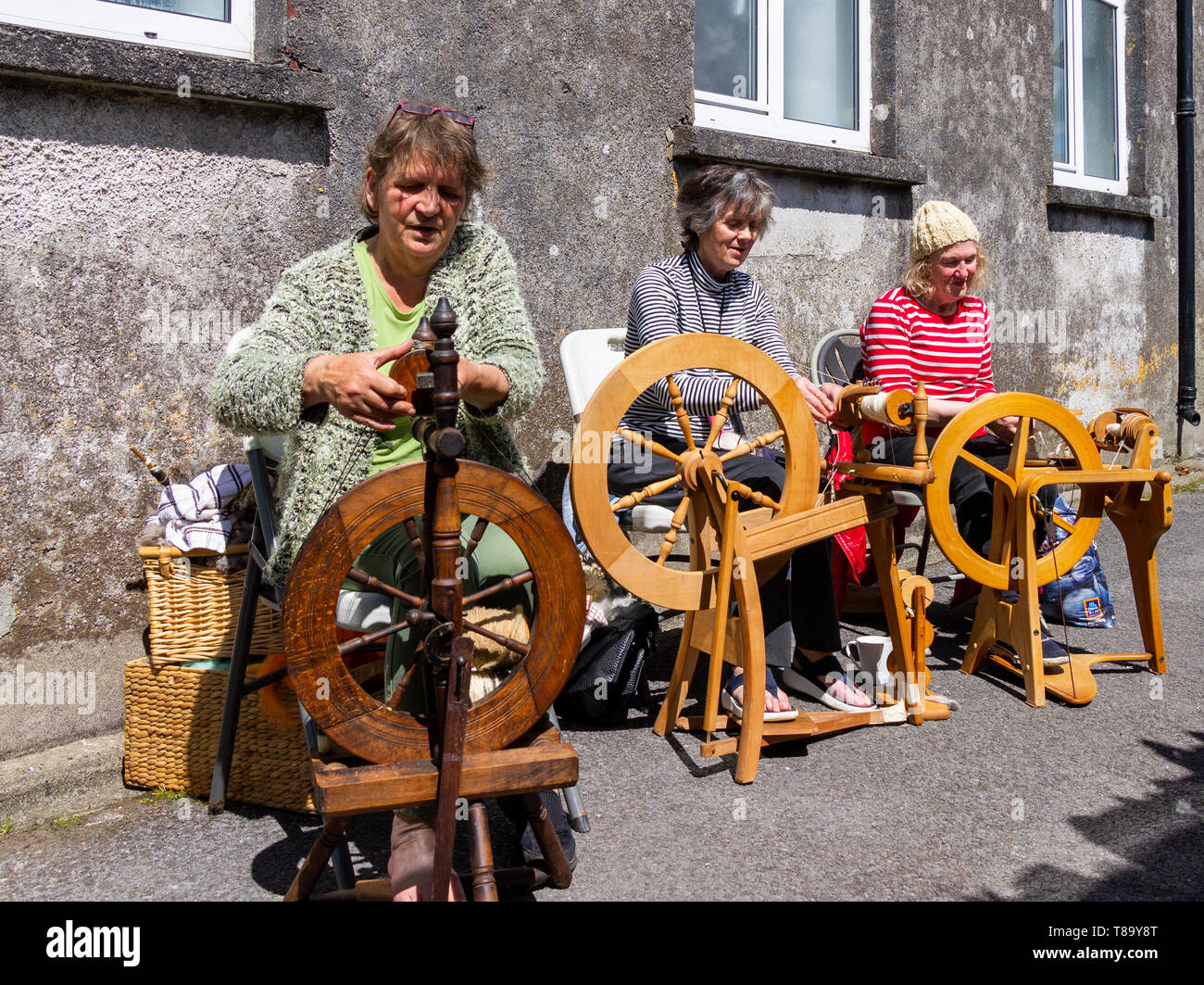 3-women-spinning-wool-outdoors-on-wooden-spinning-wheels-skibbereen-ireland-T89Y8T.jpg
