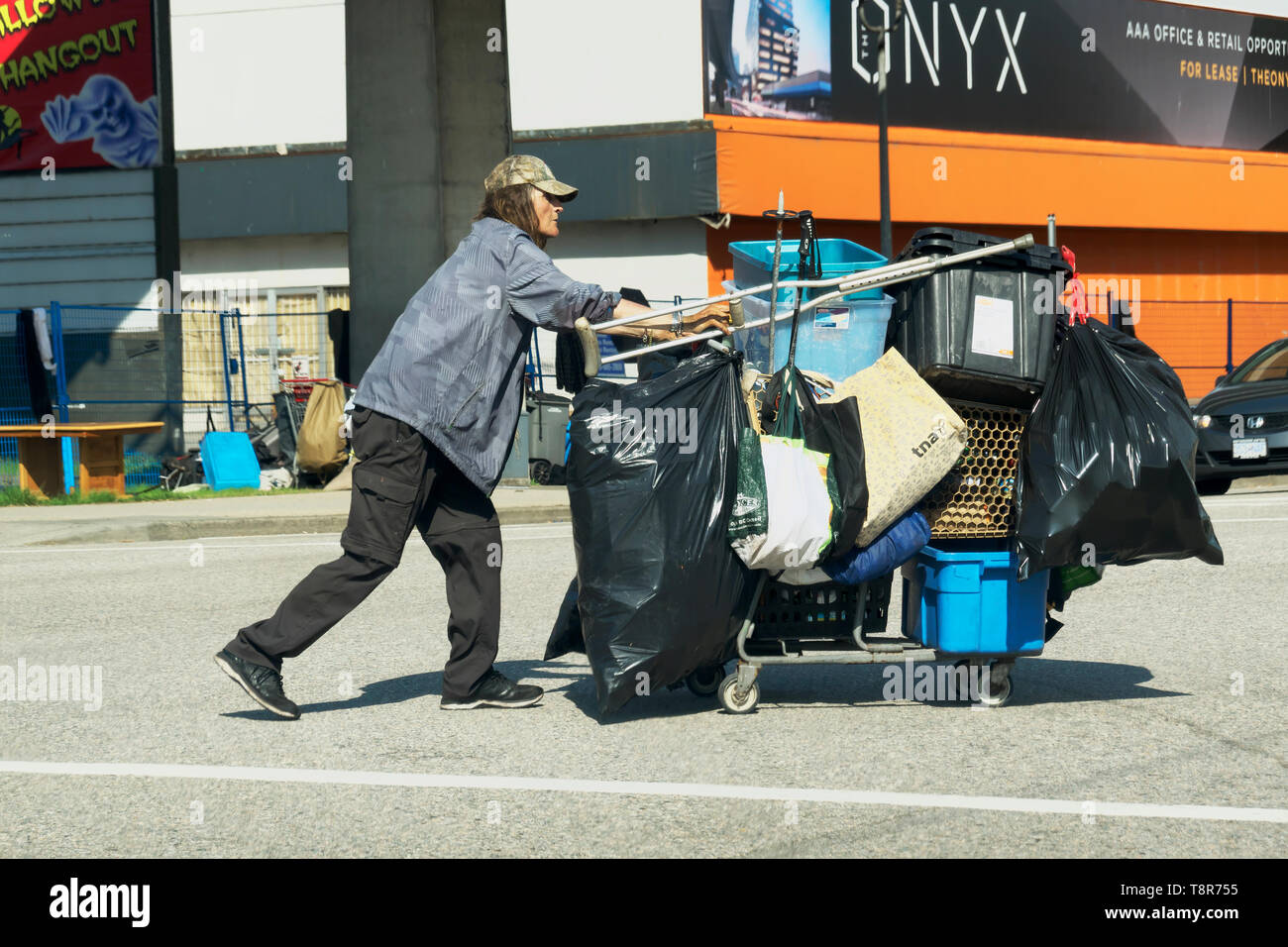 a-homeless-man-walking-across-an-intersection-pushing-a-shopping-cart-loaded-with-his-worldly-possessions-T8R755.jpg