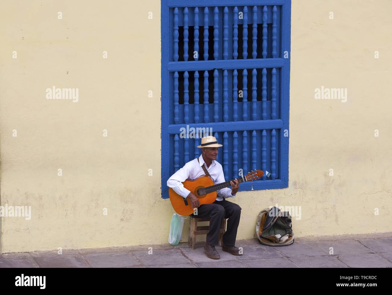 elderly-cuban-man-sitting-and-playing-gu