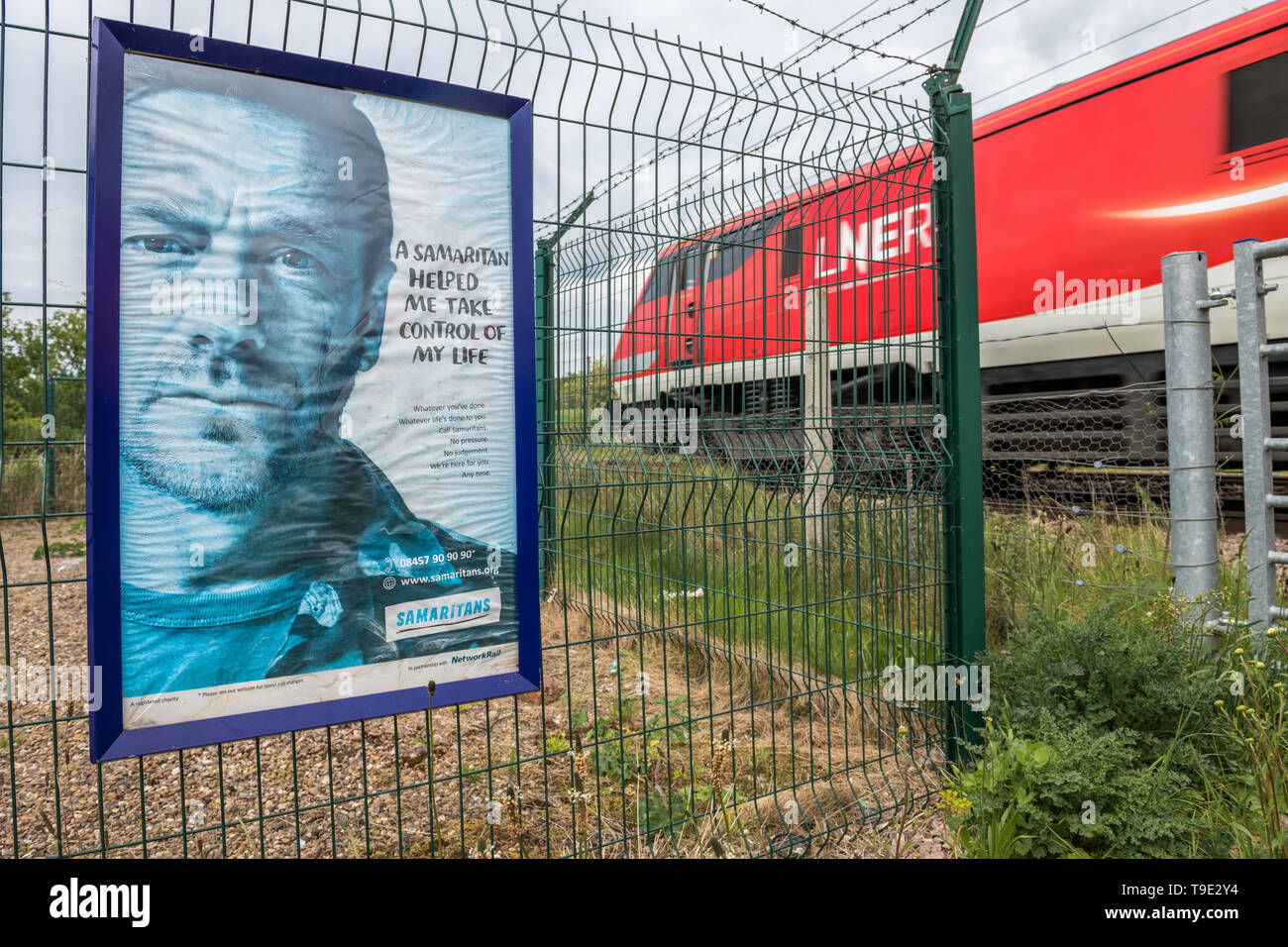 Samaritans poster 'a Samaritan helped me take control of my life' at a level crossing footpath on the East Coast Main Line railway. Stock Photo