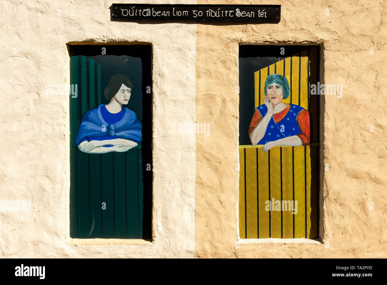 traditional-irish-cottage-detail-with-writing-in-irish-language-two-2-decorative-painted-colourful-illustrated-wooden-front-doors-of-chatting-women-TA2PYD.jpg