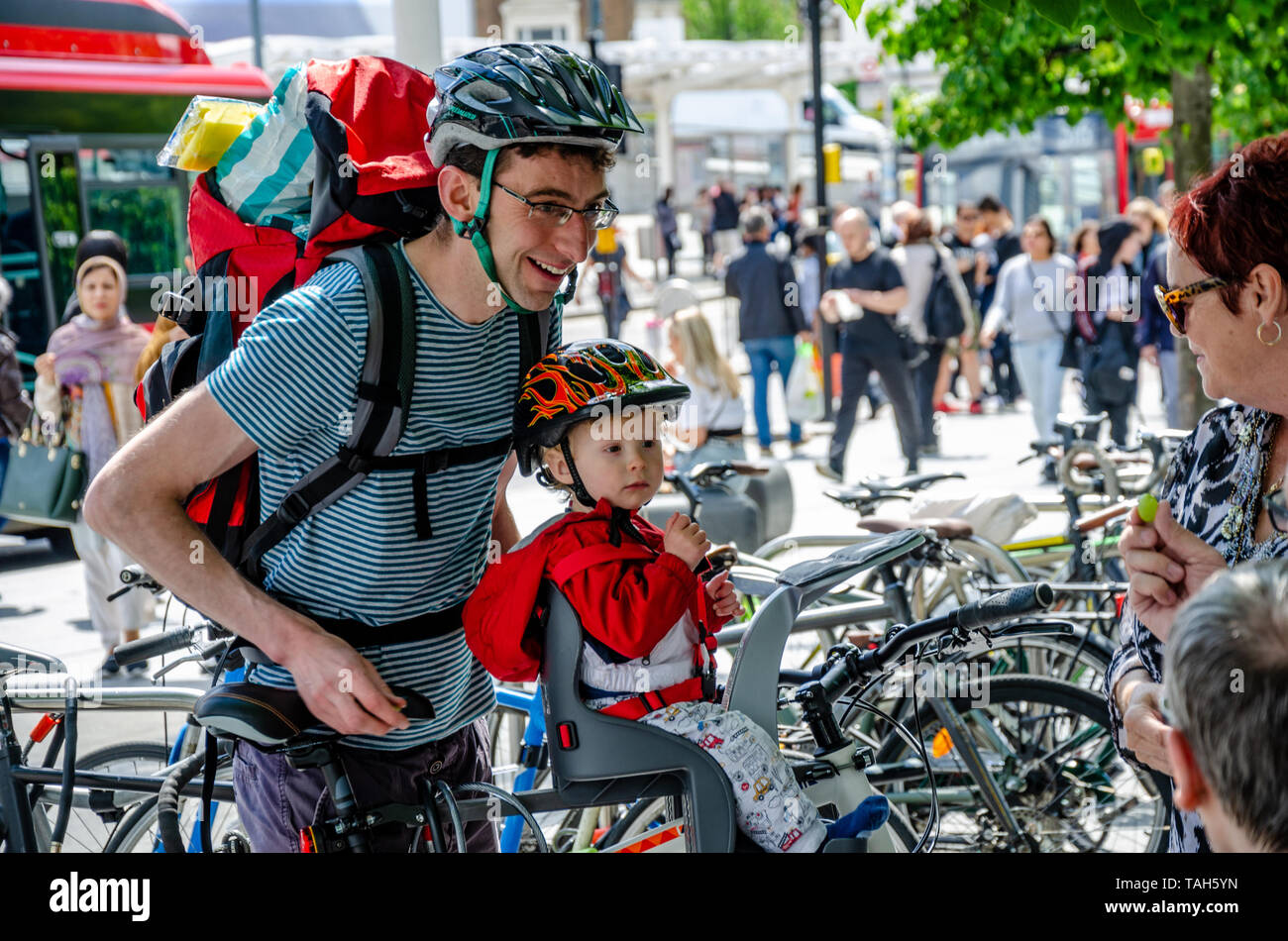 a-young-father-with-his-toddler-son-look-happy-and-smile-as-they-talk-to-a-couple-of-ladies-wearing-bicycle-helmets-ready-to-cycle-away-TAH5YN.jpg