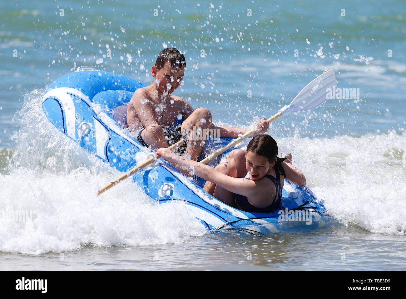 Camber, East Sussex, UK. 01 Jun, 2019. UK Weather: A beautiful sunny morning for the start of a new month as people take to the beach at Camber Sands. These youngsters enjoy themselves on a rubber dinghy splashing in the sea. © Paul Lawrenson 2019, Photo Credit: Paul Lawrenson/Alamy Live News Stock Photo