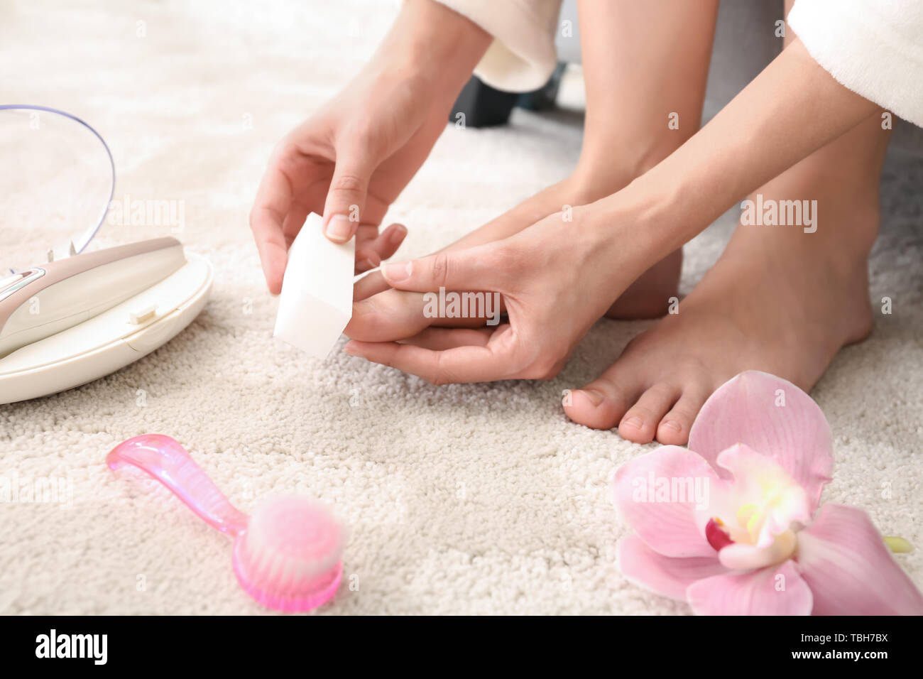 Young woman polishing her nails at home Stock Photo