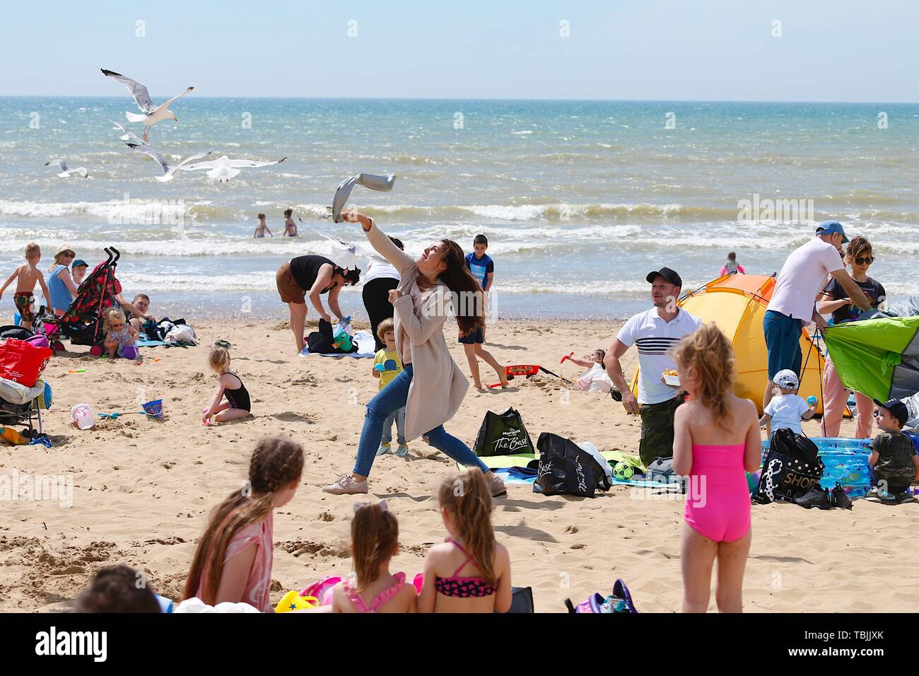 Camber, East Sussex, UK. 02 Jun, 2019. UK Weather: The weekend continues with hot and sunny weather with only a slight breeze in the air at Camber Sands in East Sussex on the South East coast, temperatures are expected to be slightly lower than the highs of Saturday. The dangers of eating on the beach as this lady tries to scare away the seagulls. © Paul Lawrenson 2019, Photo Credit: Paul Lawrenson/Alamy Live News Stock Photo