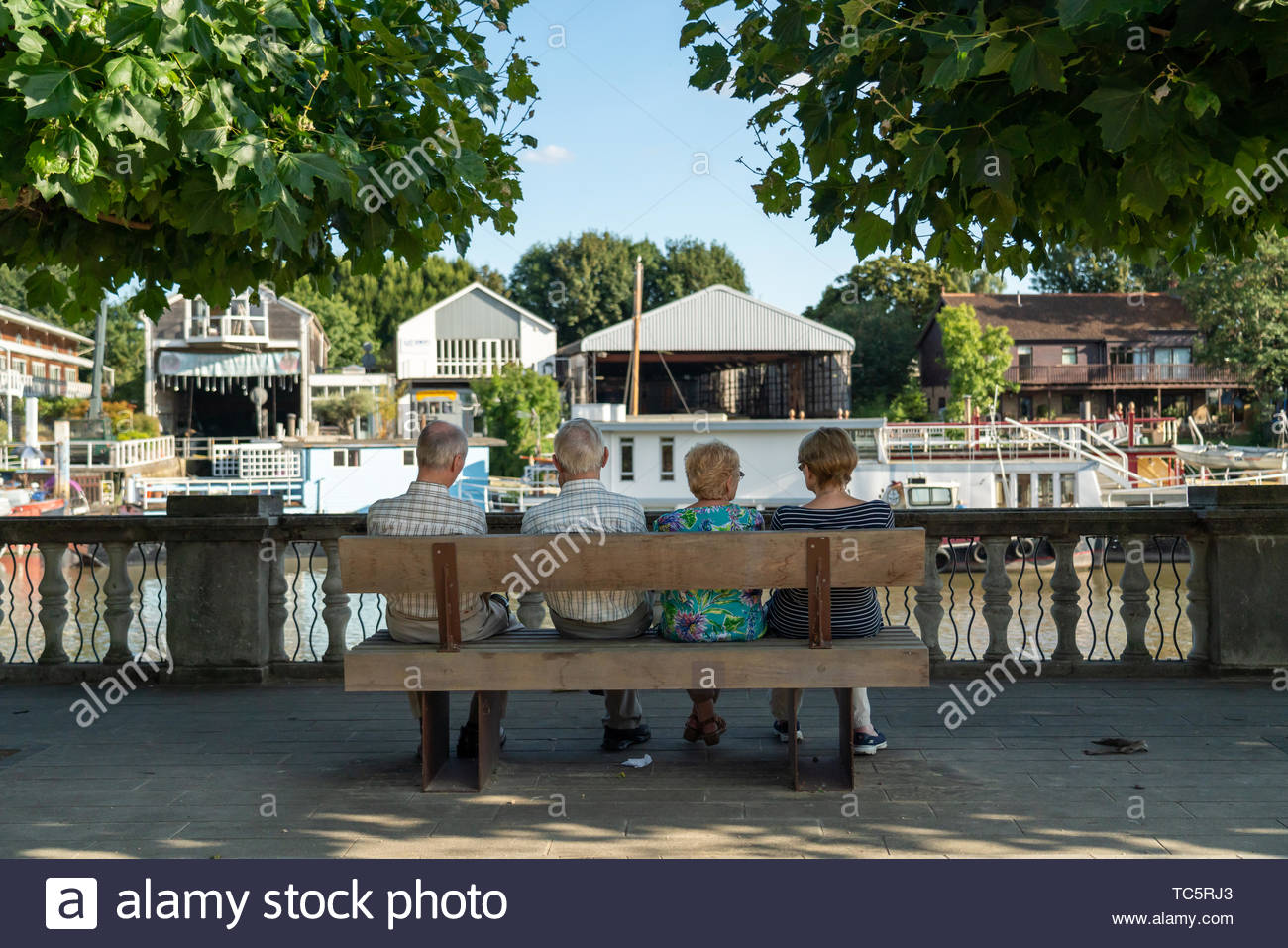 Two mature couples enjoying some shade on  a sunny summer afternoon along the Thames in Twickenham, UK Stock Photo