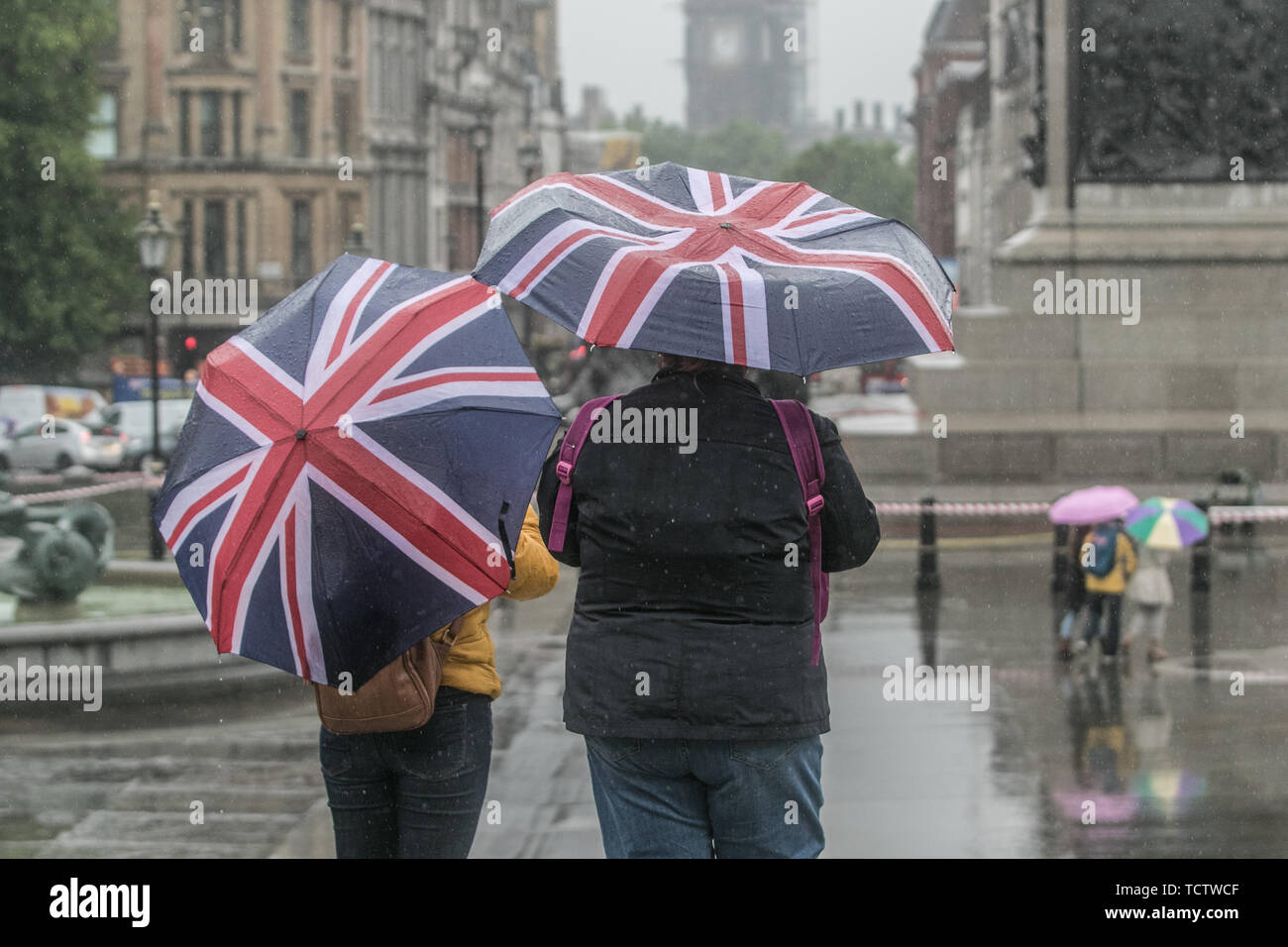 London, UK. 10th June, 2019. Pedestrians brave the heavy rain in Trafalgar Square on a cold and wet day in London Credit: amer ghazzal/Alamy Live News Stock Photo