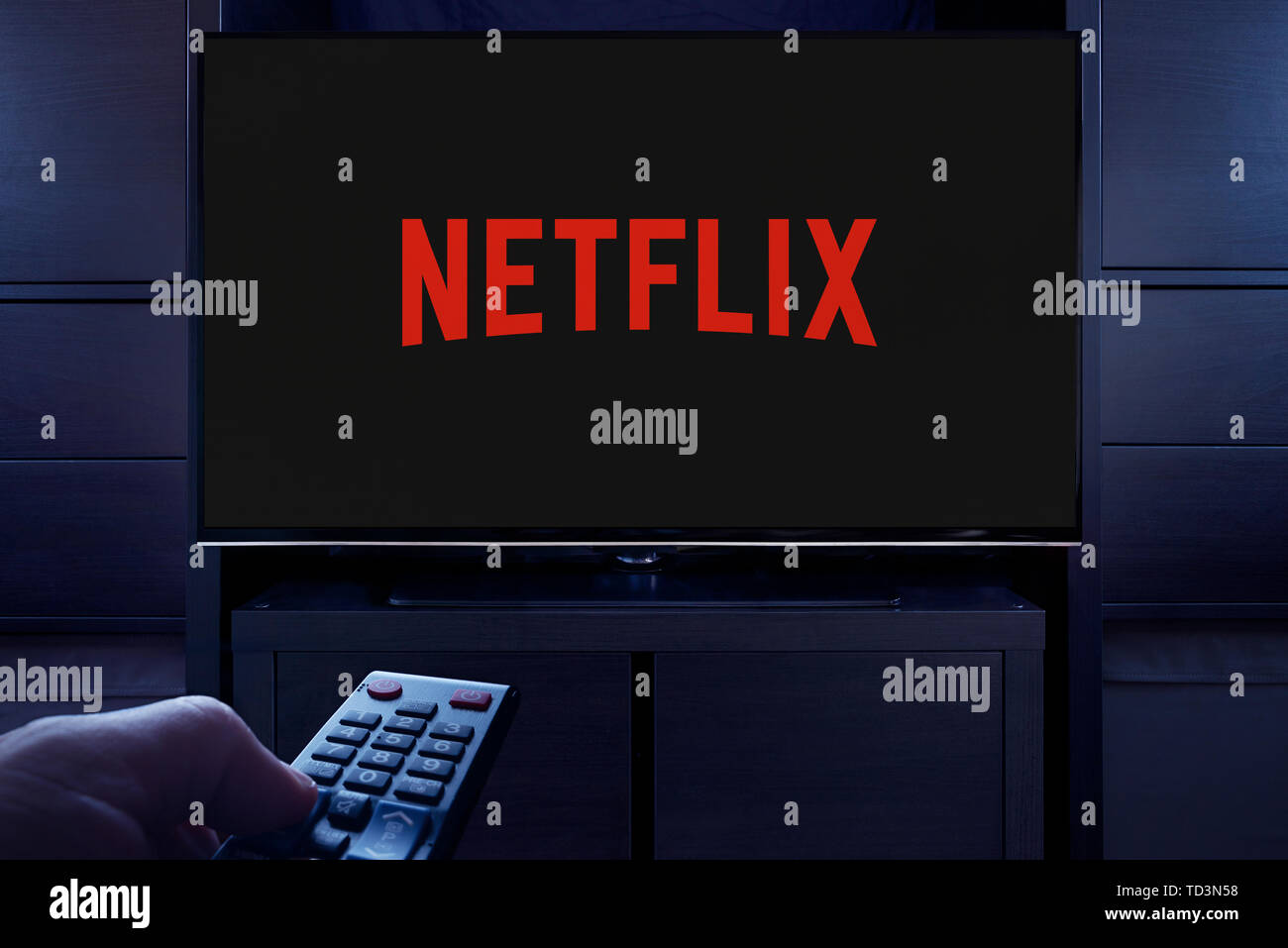 A man points a TV remote at the television which displays the logo for the Netflix on demand video streaming service (Editorial use only). Stock Photo