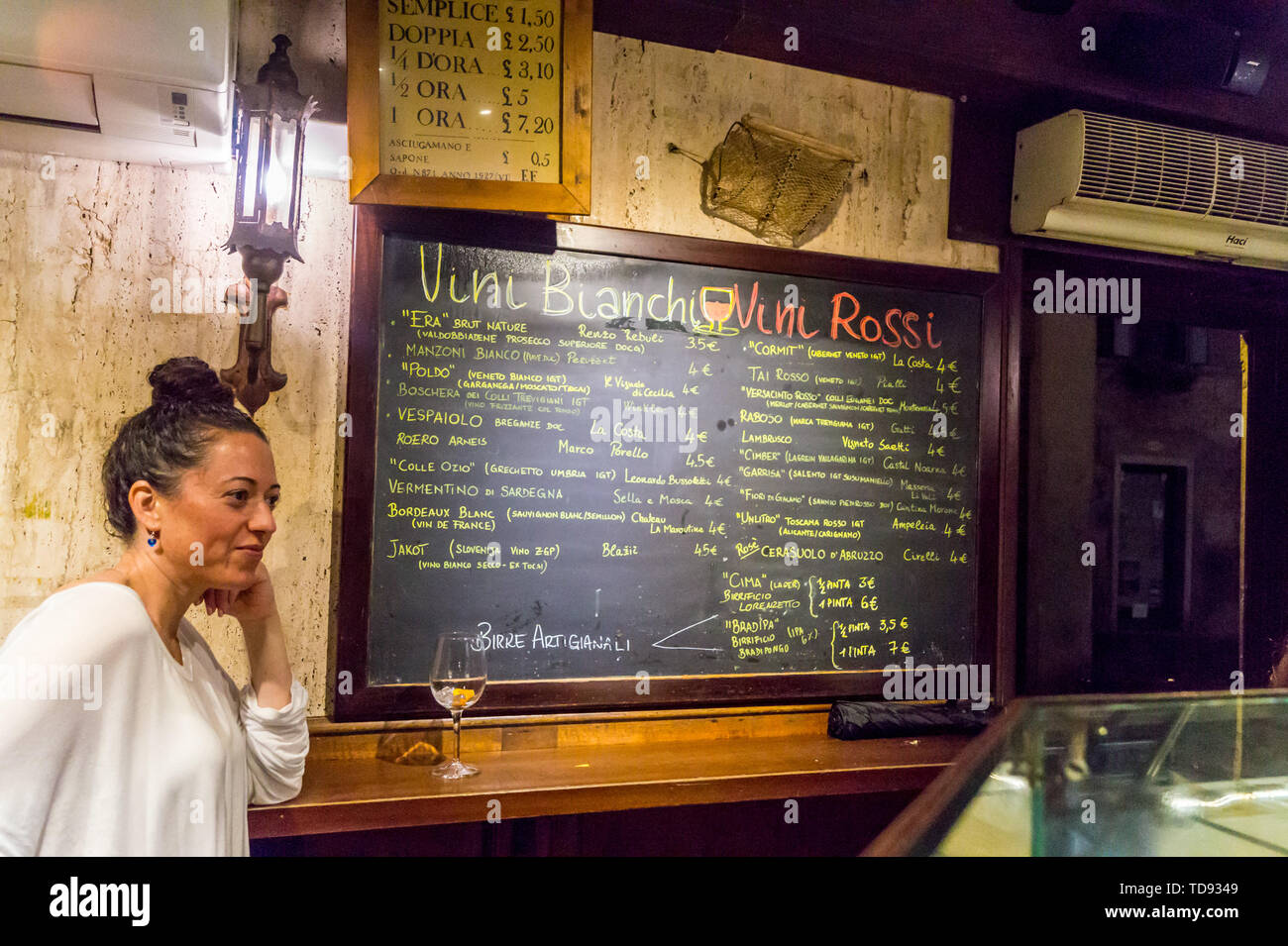 a-young-woman-with-a-glass-of-white-wine-by-the-wine-menu-on-a-blackboard-at-osteria-al-portego-wine-bar-venice-veneto-italy-TD9349.jpg